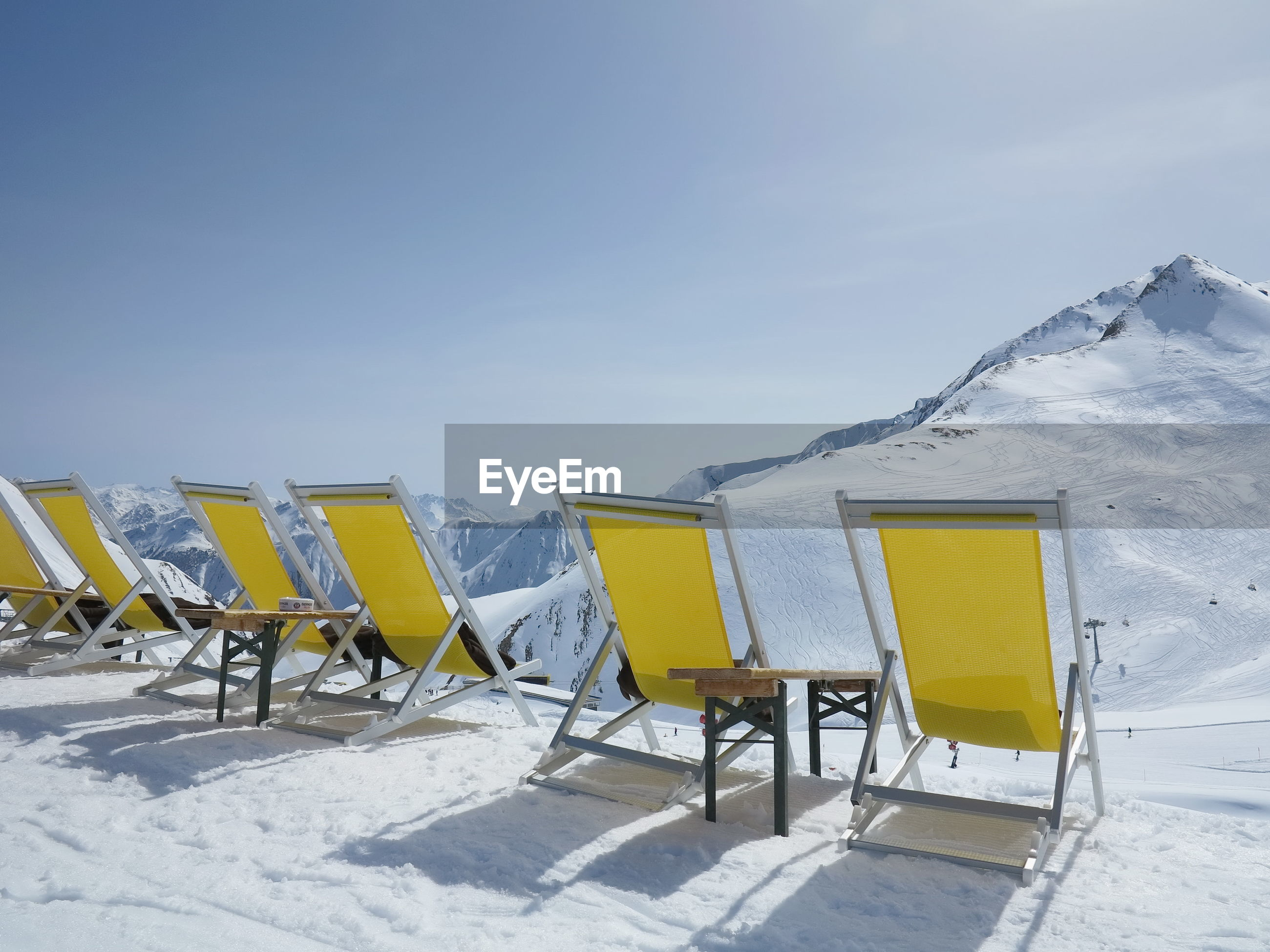 Empty yellow deck chairs by snow covered mountain against clear sky