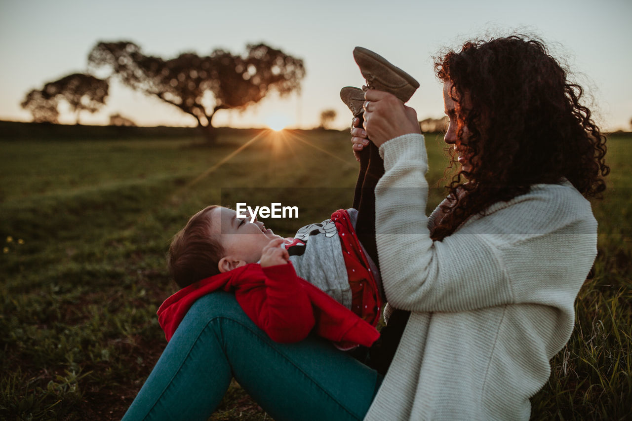 real people, women, child, two people, females, leisure activity, field, sunset, side view, land, lifestyles, childhood, holding, nature, family, togetherness, sky, focus on foreground, girls, wireless technology, outdoors, positive emotion