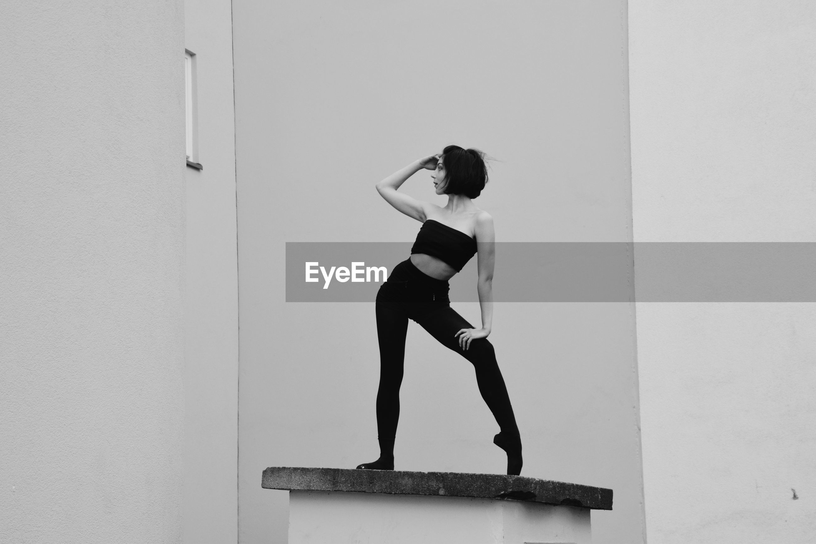 WOMAN STANDING ON WALL