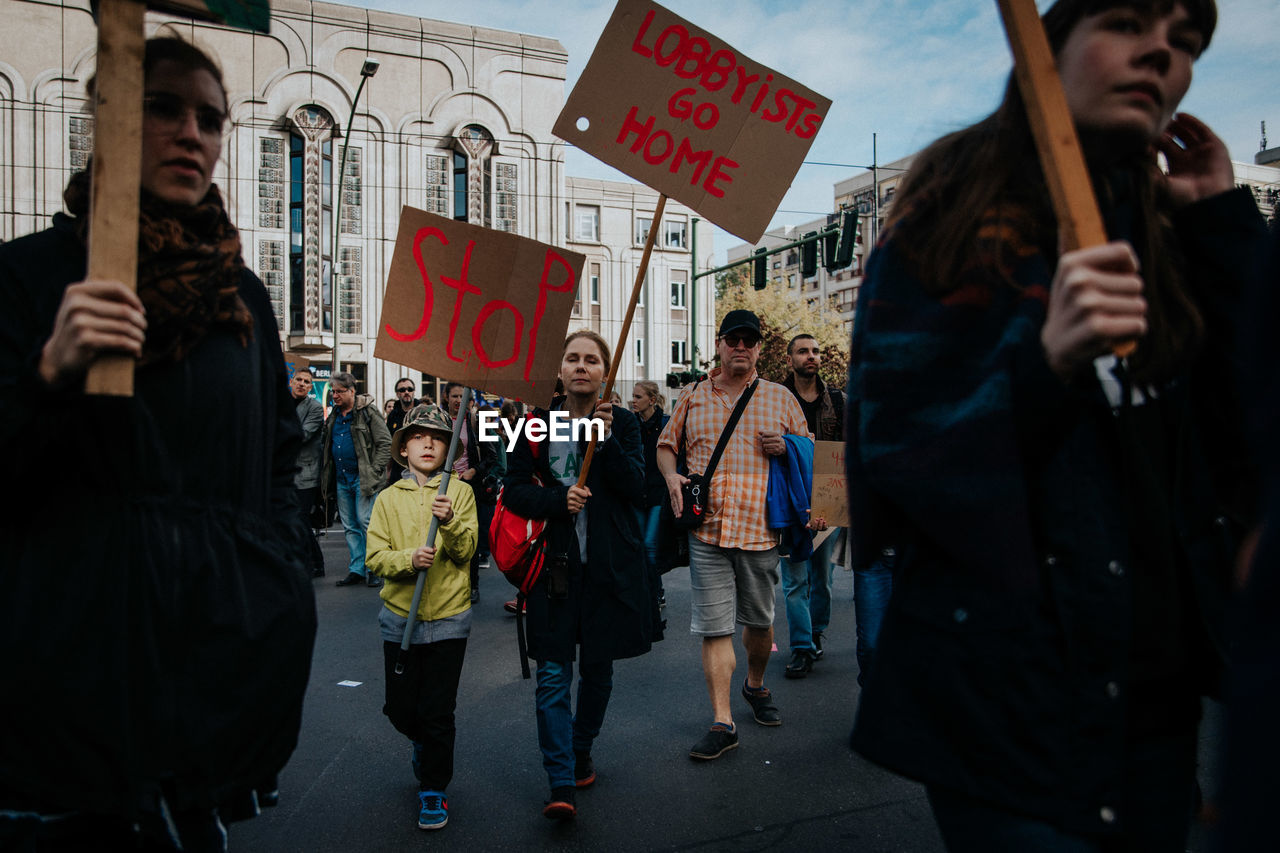 city, group of people, real people, street, communication, men, architecture, women, text, lifestyles, people, building exterior, city life, crowd, built structure, protest, script, adult, non-western script, outdoors, protestor