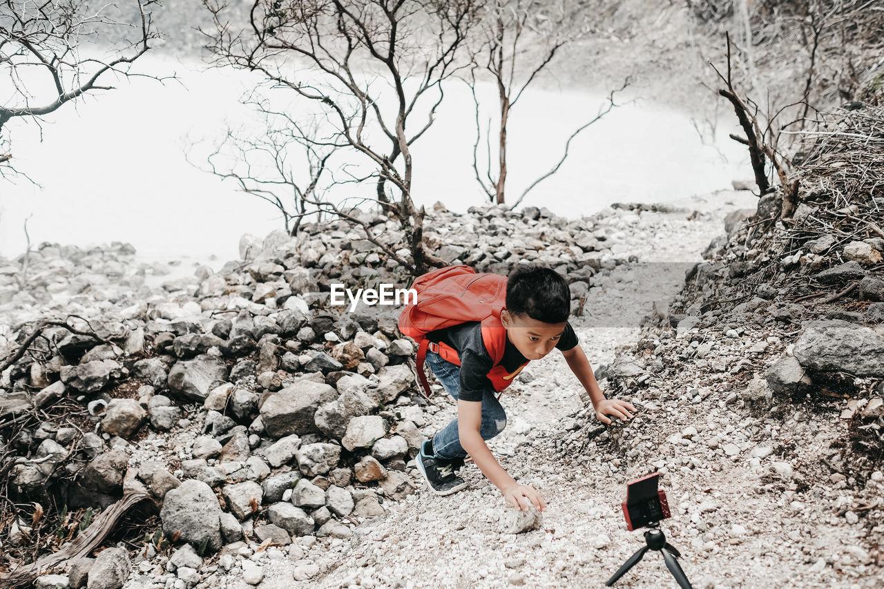 Full Length Of Boy Reaching Smart Phone Against Lake