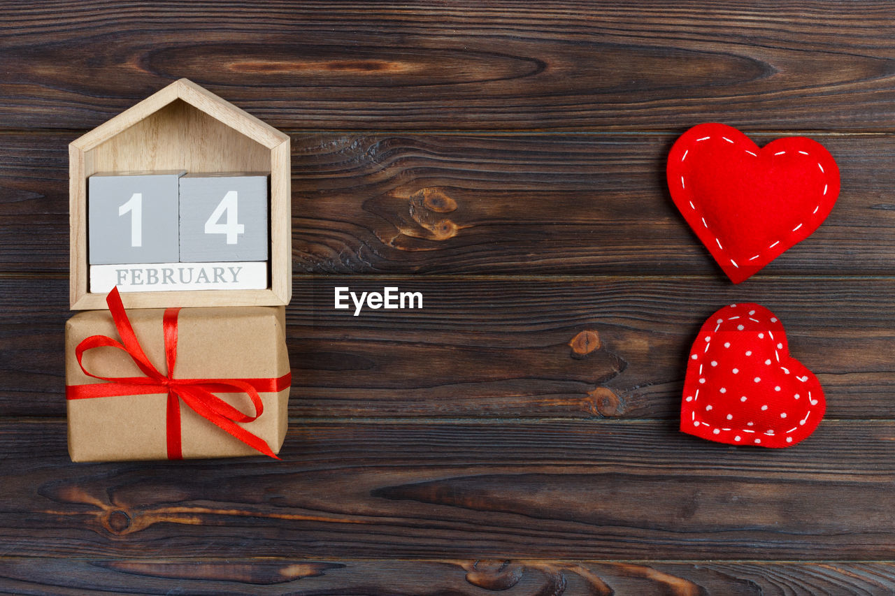 wood - material, red, emotion, directly above, indoors, heart shape, table, communication, no people, positive emotion, still life, close-up, western script, love, text, wood, box - container, box, shape, celebration, valentine's day - holiday, wood grain