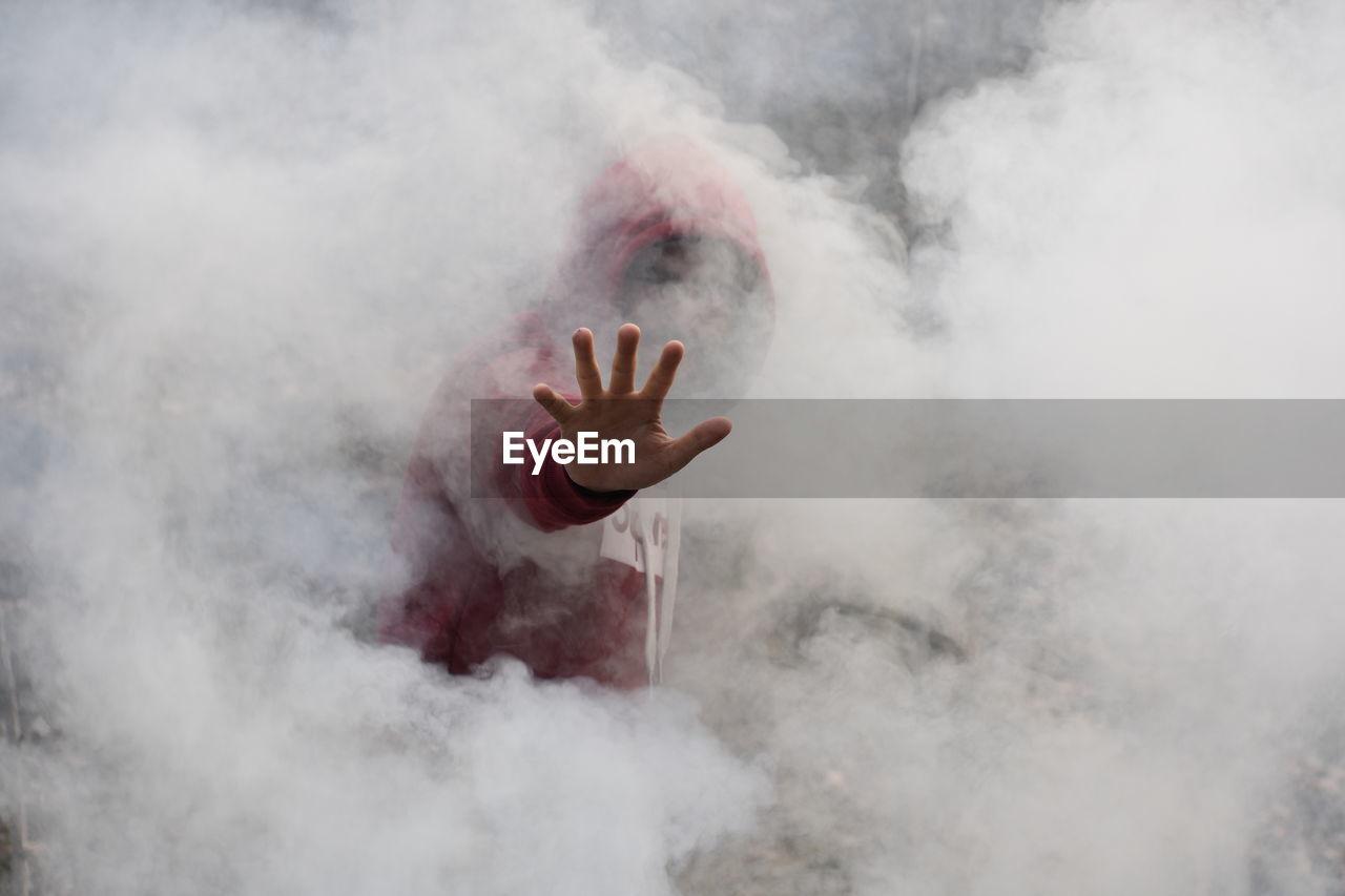 Man in hood standing amidst smoke