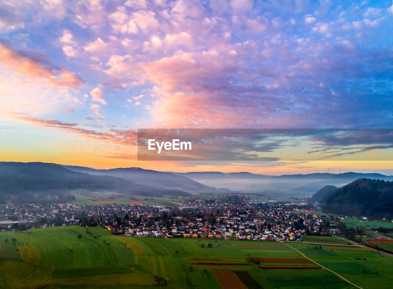 Aerial view of town and mountains against cloudy sky during sunset