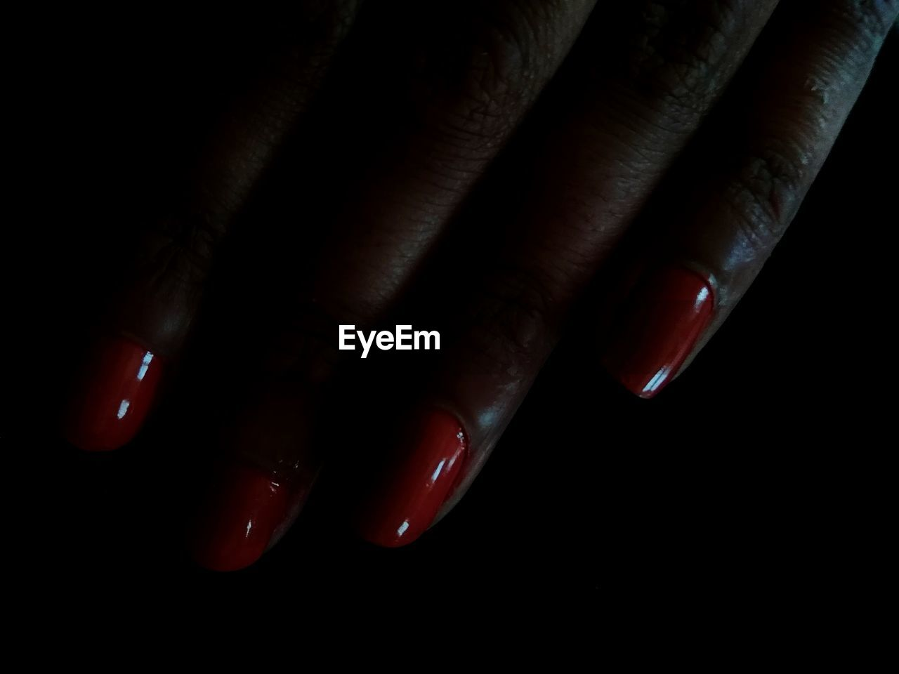 Cropped Hand Of Woman With Red Nail Polish Against Black Background