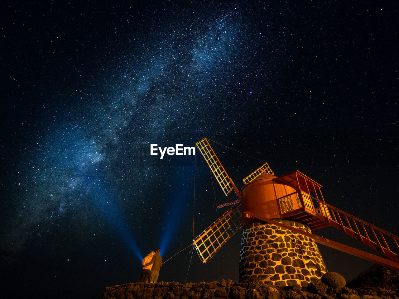 Low angle view of couple standing by windmill against star field at night