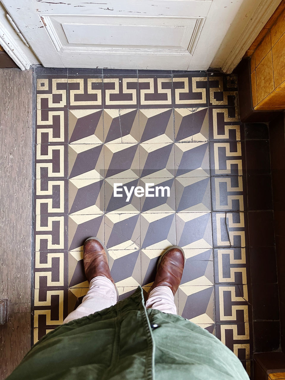 LOW SECTION OF MAN STANDING BY TILED FLOOR