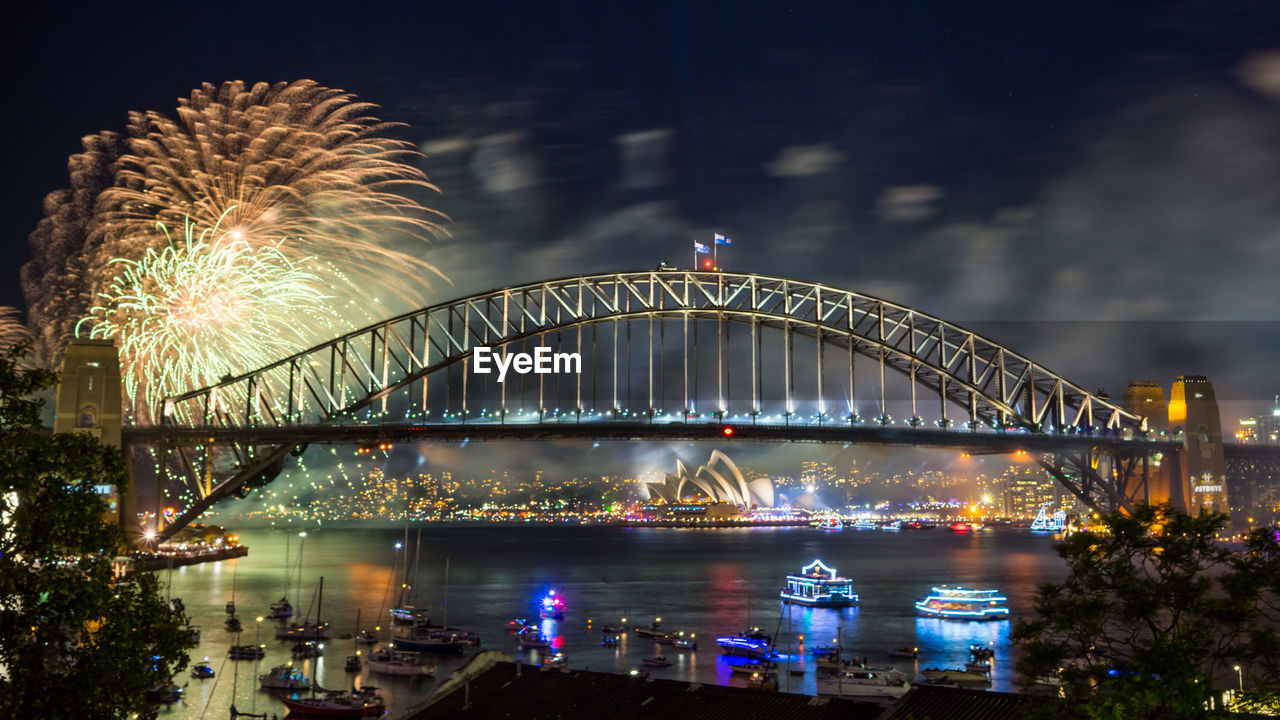 Sydney Harbor Bridge Over Parramatta River With Firework Display Against Sky At Night