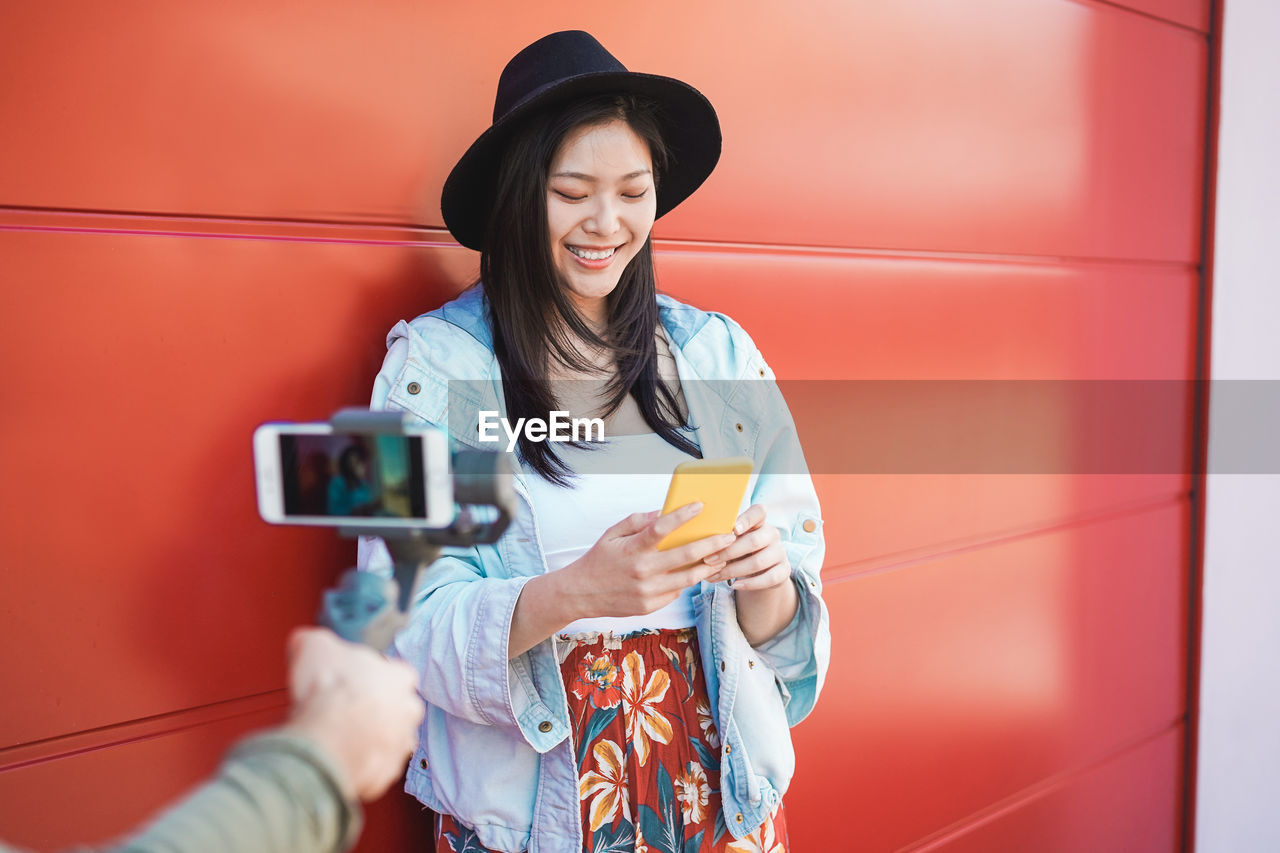 technology, wireless technology, portable information device, mobile phone, smart phone, holding, real people, lifestyles, photography themes, connection, young adult, communication, women, young women, photographing, activity, one person, smiling, leisure activity, camera, hairstyle