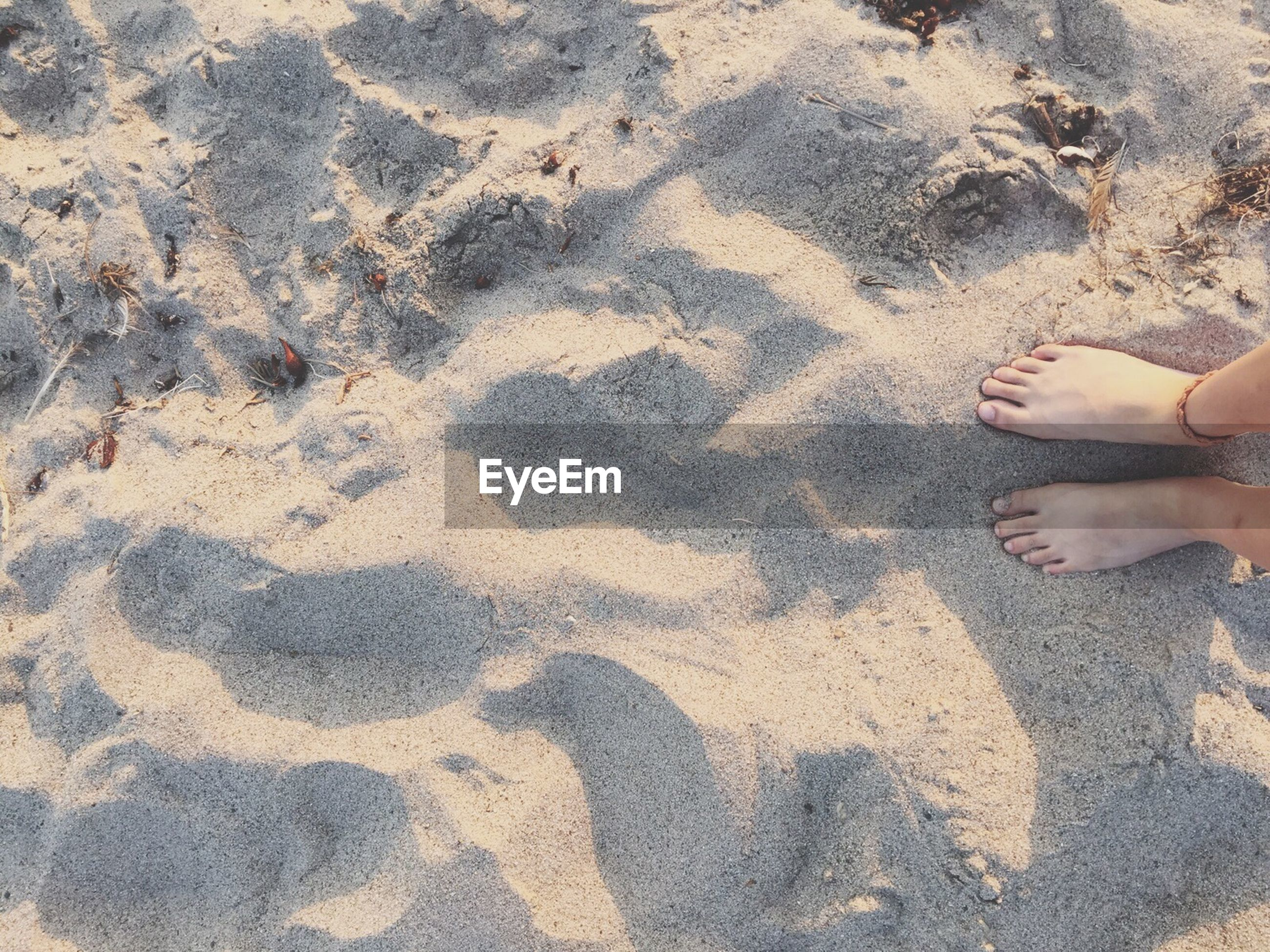 sand, beach, high angle view, low section, lifestyles, leisure activity, person, shadow, sunlight, standing, men, human foot, unrecognizable person, shore, outdoors, footprint