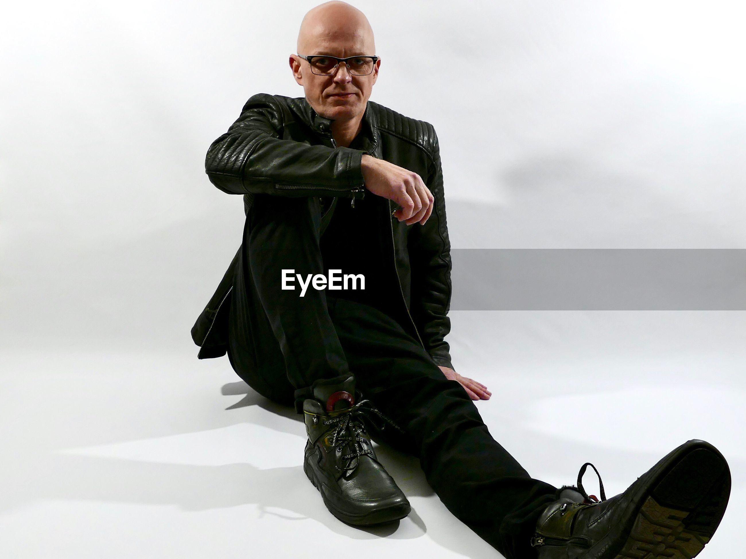 Full length portrait of man wearing leather jacket against white background