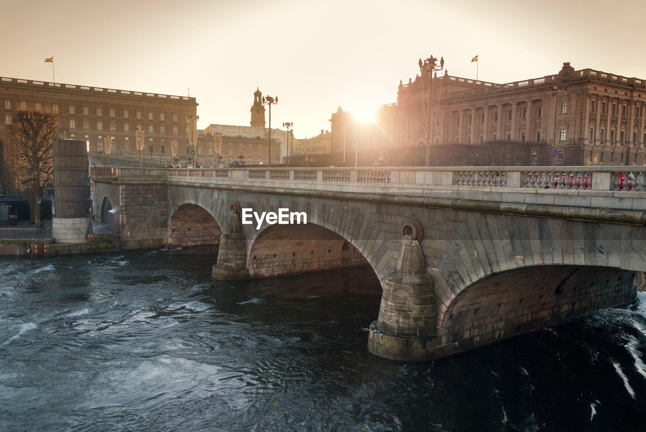 Arch bridge by historic buildings against sky