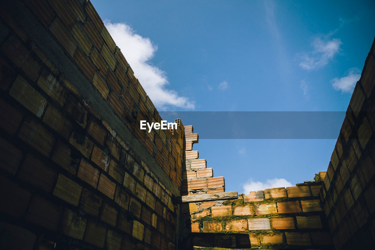 Low Angle View Of Brick Wall Against Blue Sky