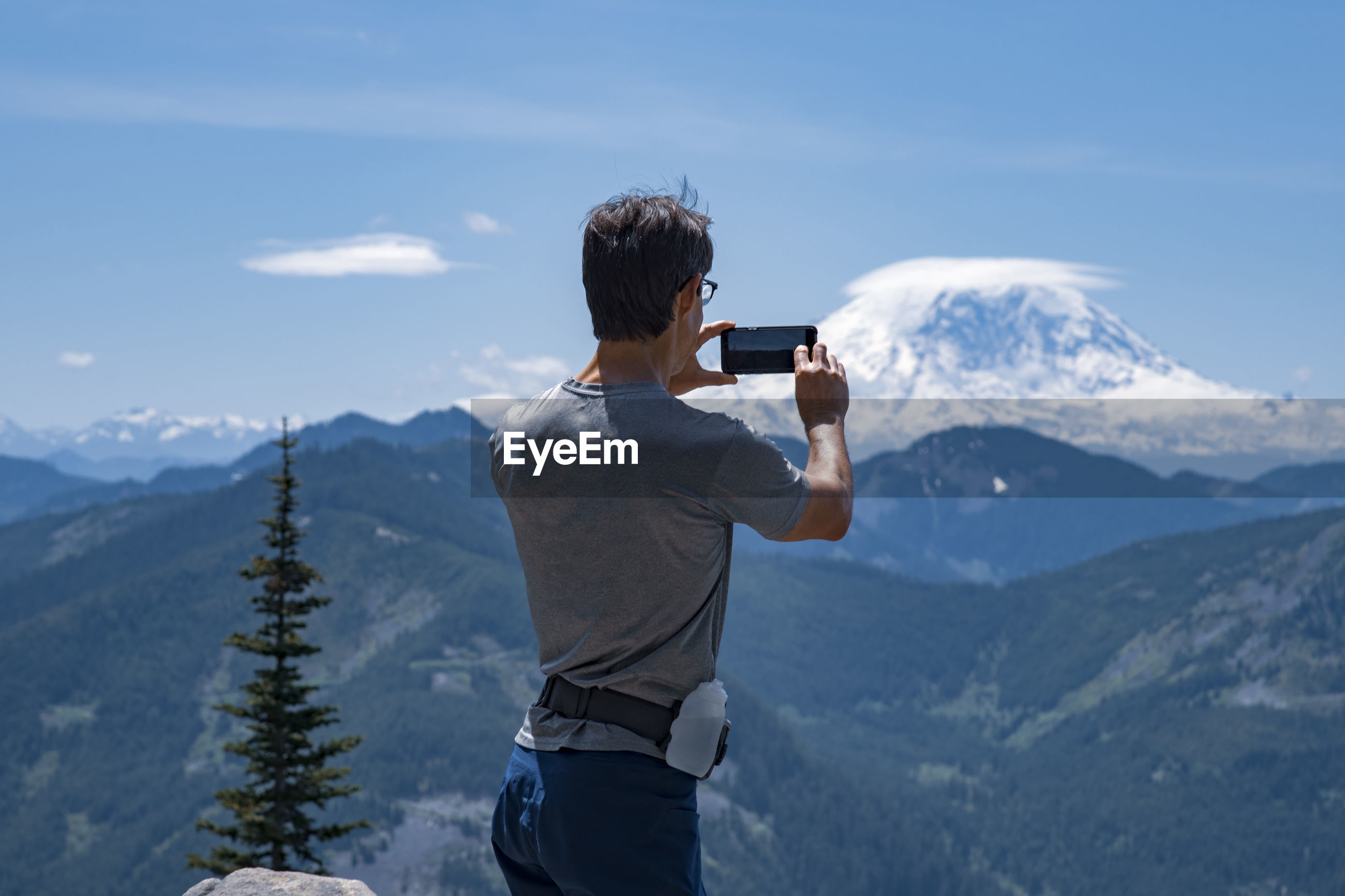 Rear view of man photographing mountains against sky