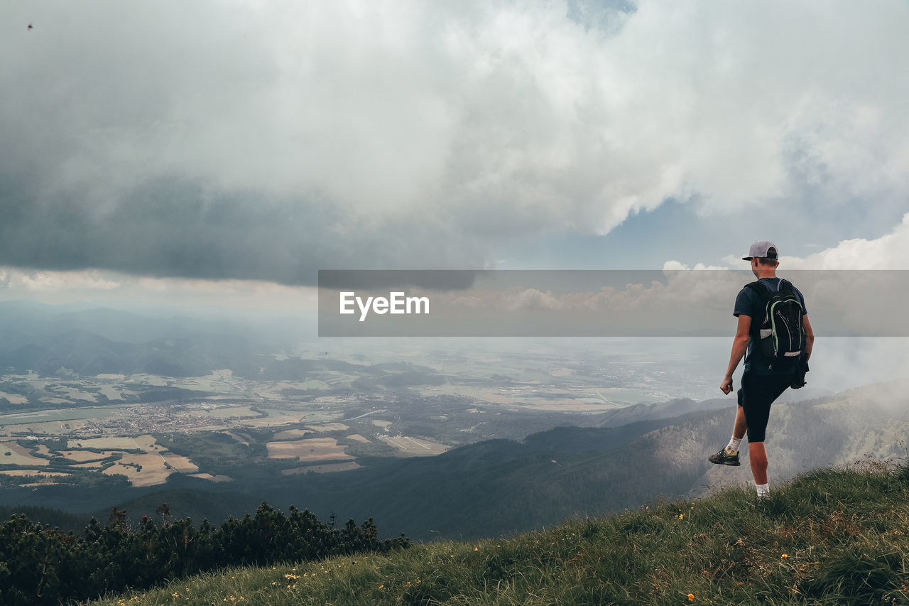 Blonde athlete poses on top of the mala fatra mountain. climbing mount hromova. a hiker walks along