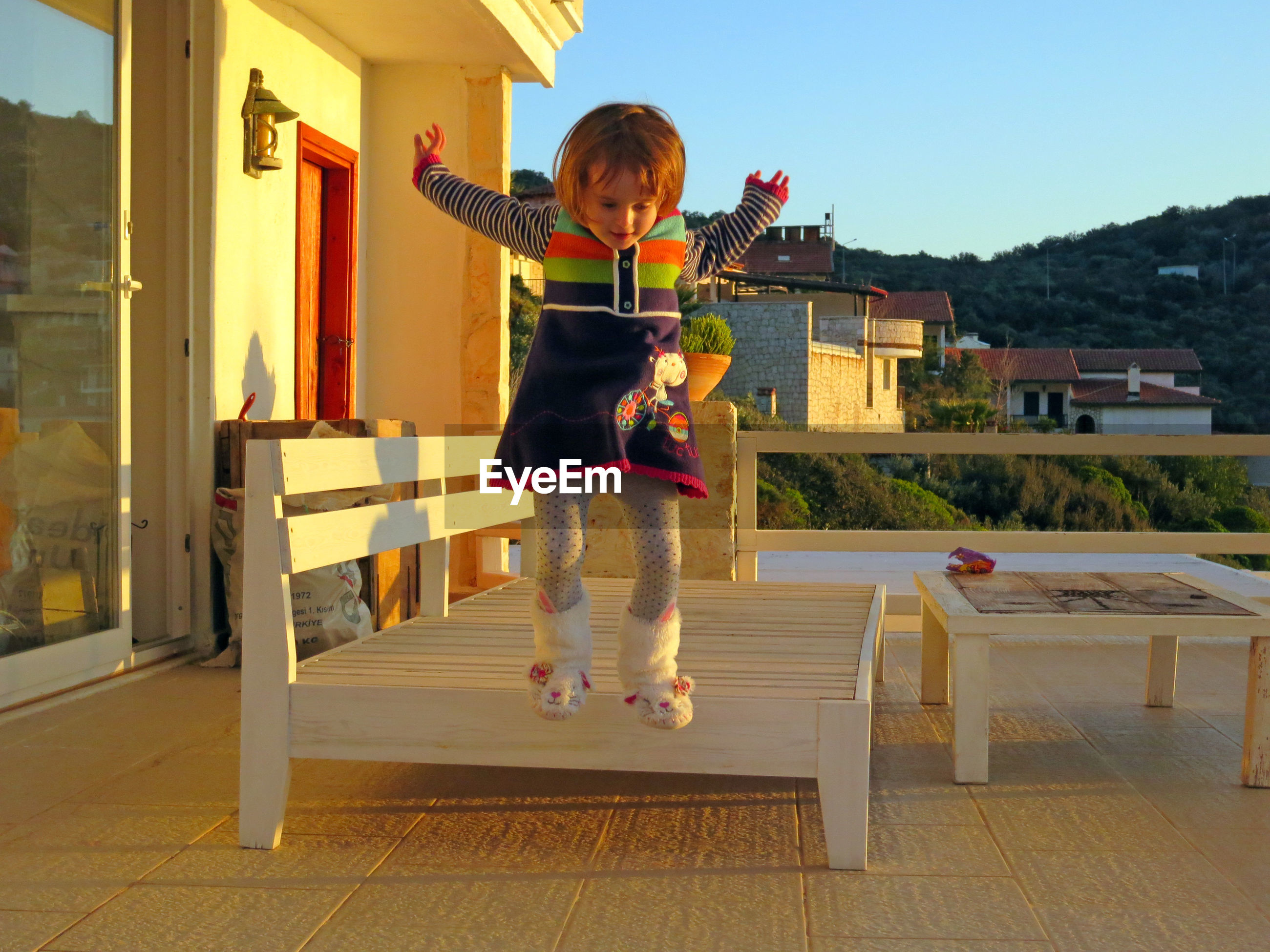 Full length of girl with arms raised jumping at home