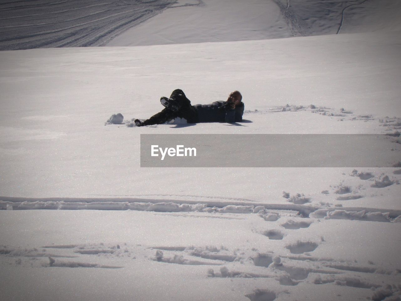 MAN LYING ON SNOW COVERED FIELD