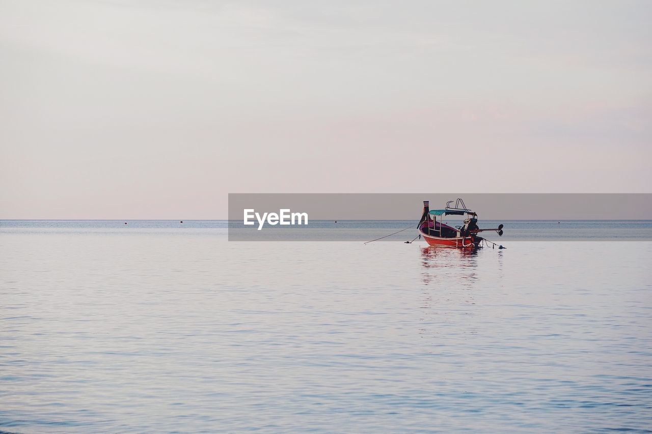 Fisherman Standing In Boat While Sailing At Sea Against Sky