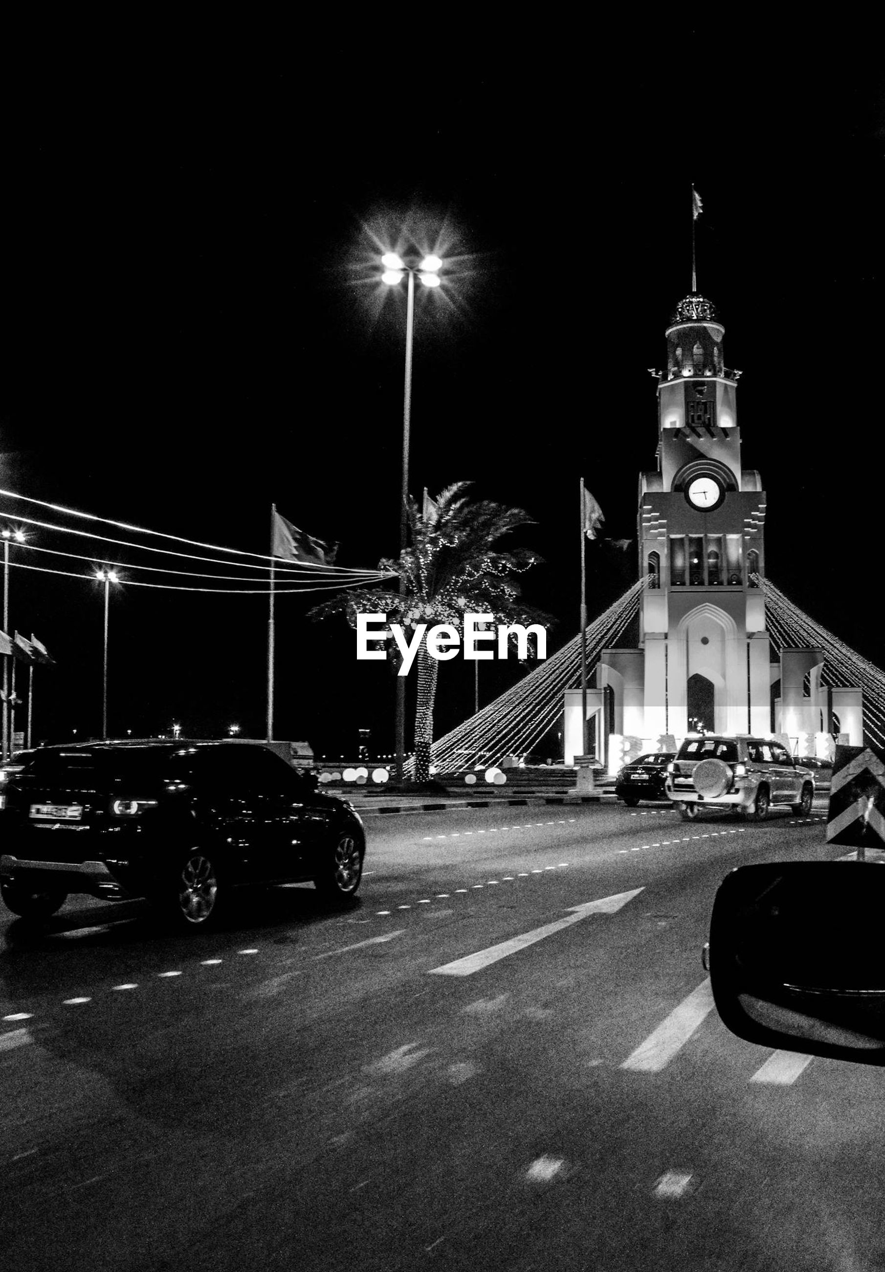 car, land vehicle, transportation, night, illuminated, architecture, building exterior, built structure, street, mode of transport, road, street light, city, city street, traffic, travel, sky, clear sky, city life, clock tower