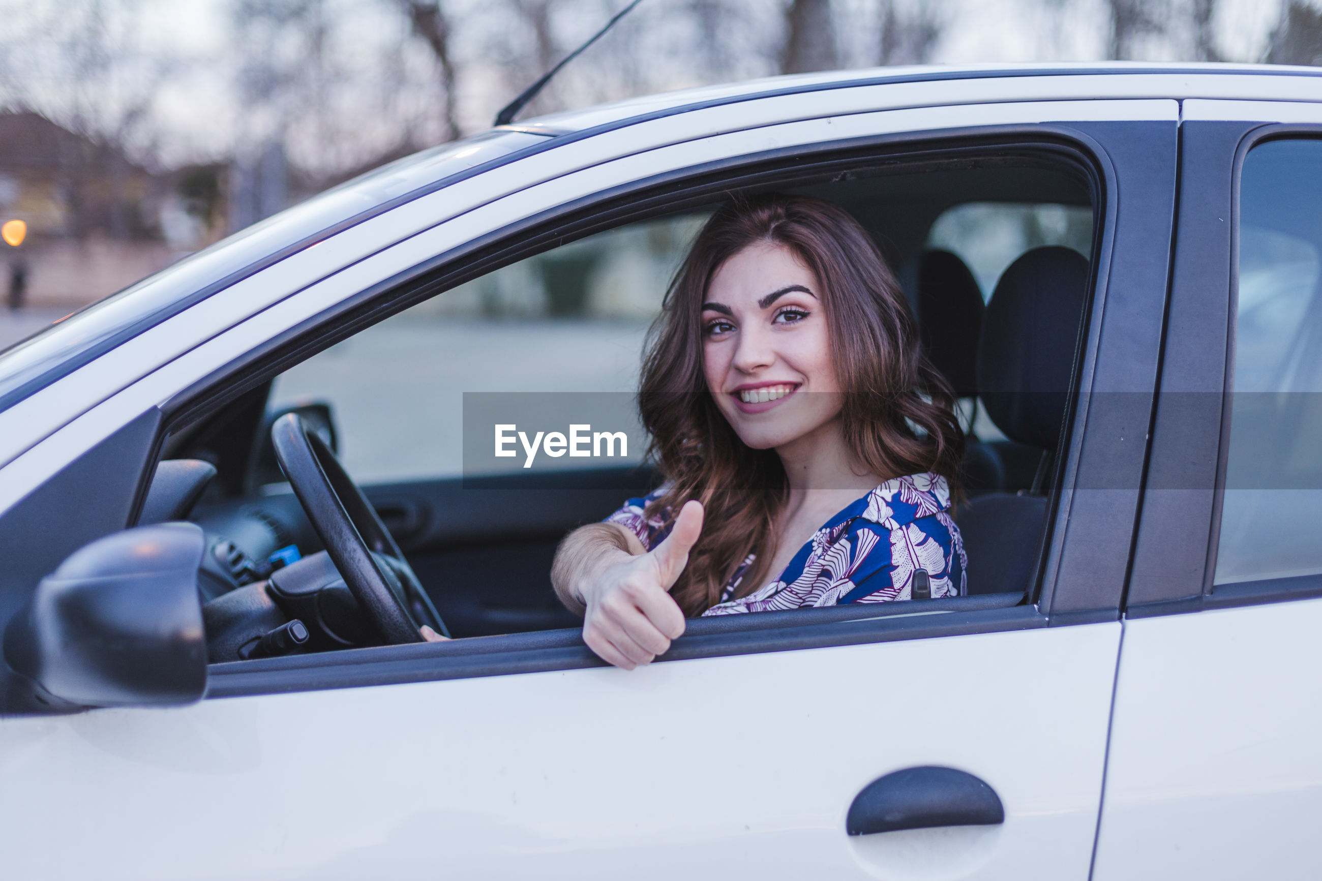 Portrait of young woman gesturing thumbs up sign in car