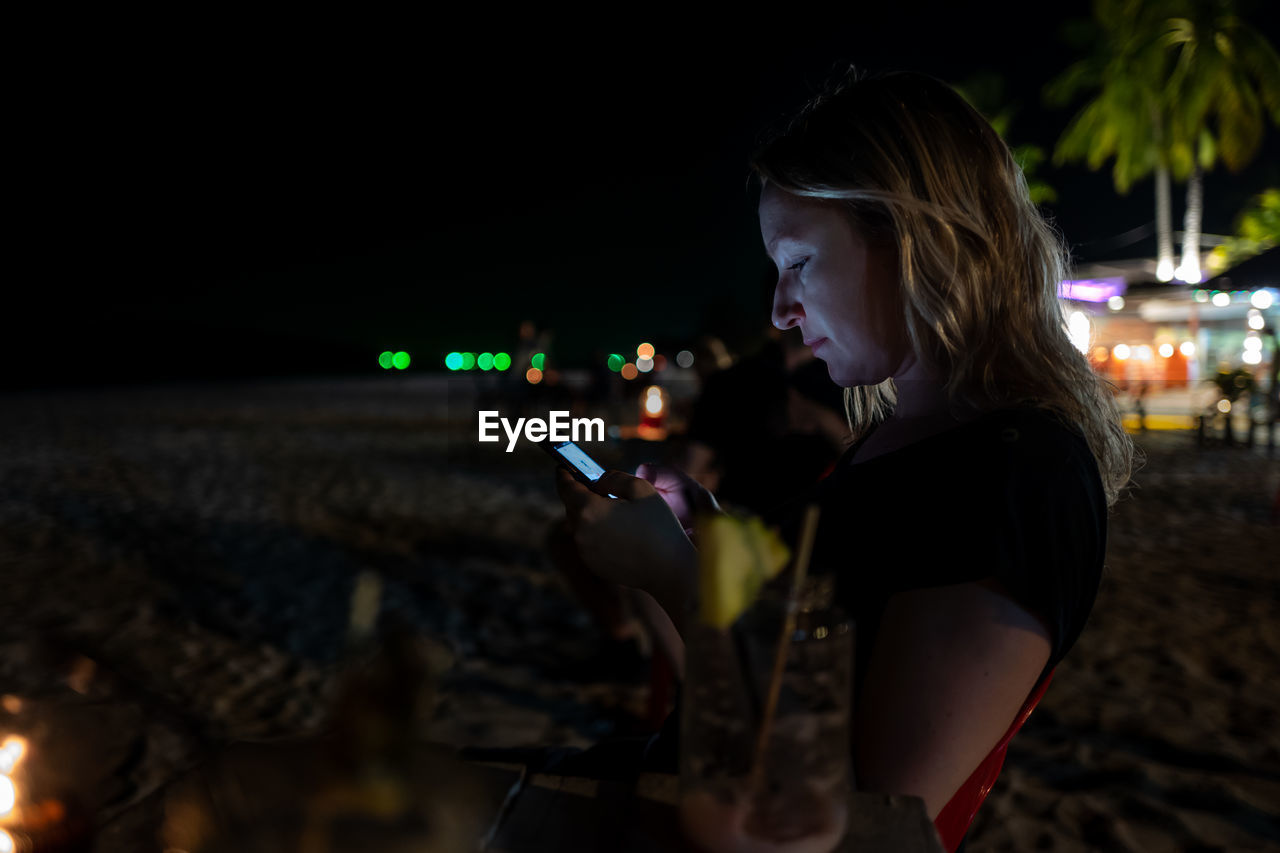 night, one person, wireless technology, technology, illuminated, lifestyles, holding, communication, real people, portable information device, young adult, smart phone, mobile phone, connection, using phone, young women, leisure activity, adult, side view, hair, hairstyle, outdoors