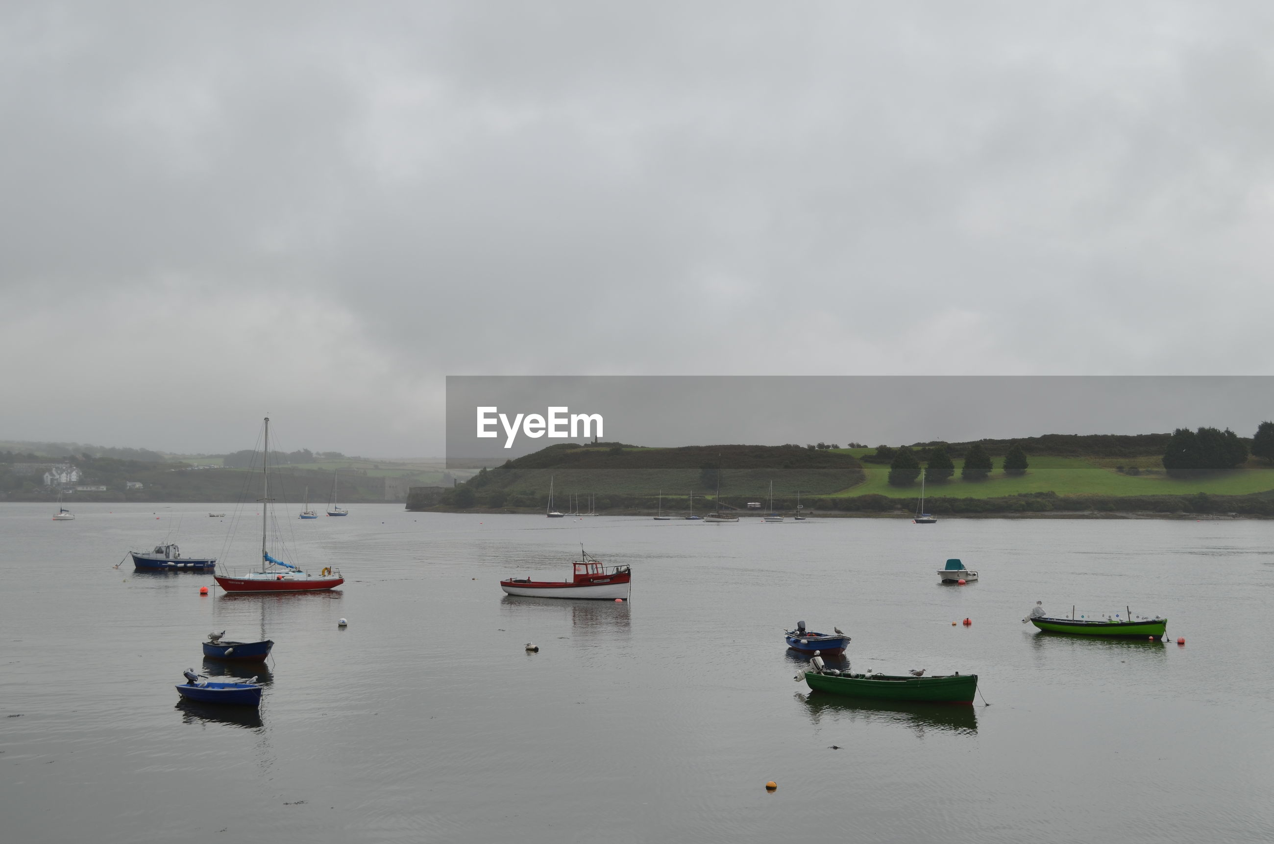 BOATS IN RIVER BY SEA AGAINST CLOUDY SKY