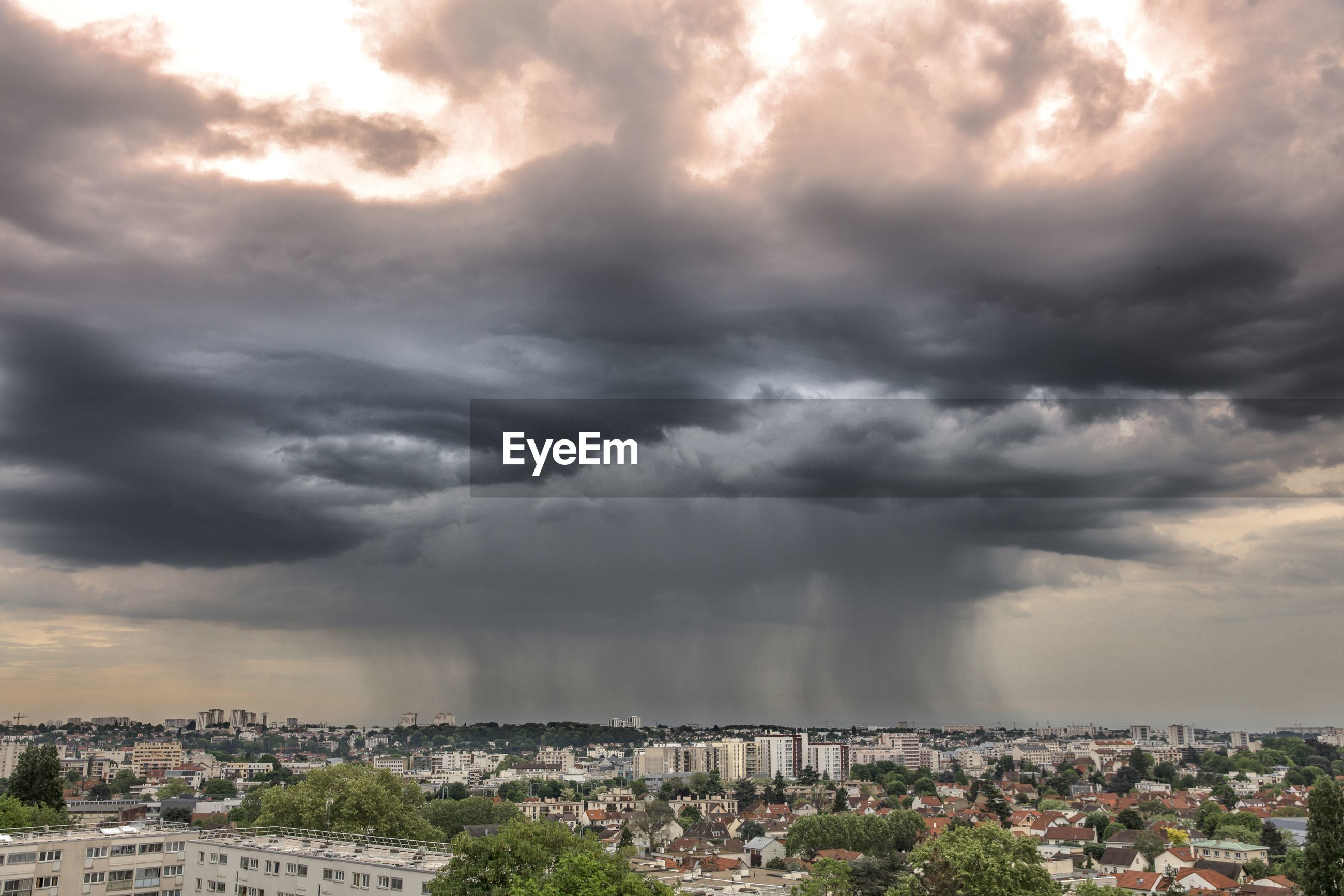 Aerial view of city against dramatic sky