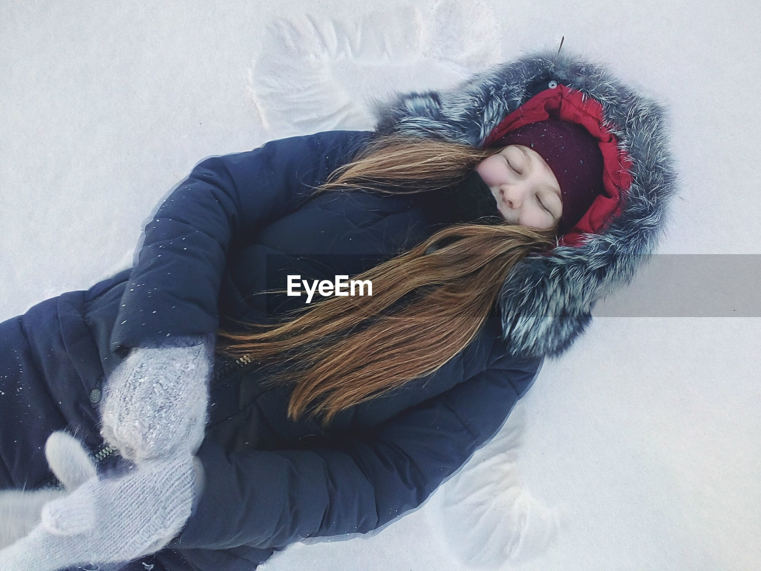 Woman in warm clothing lying down on snow