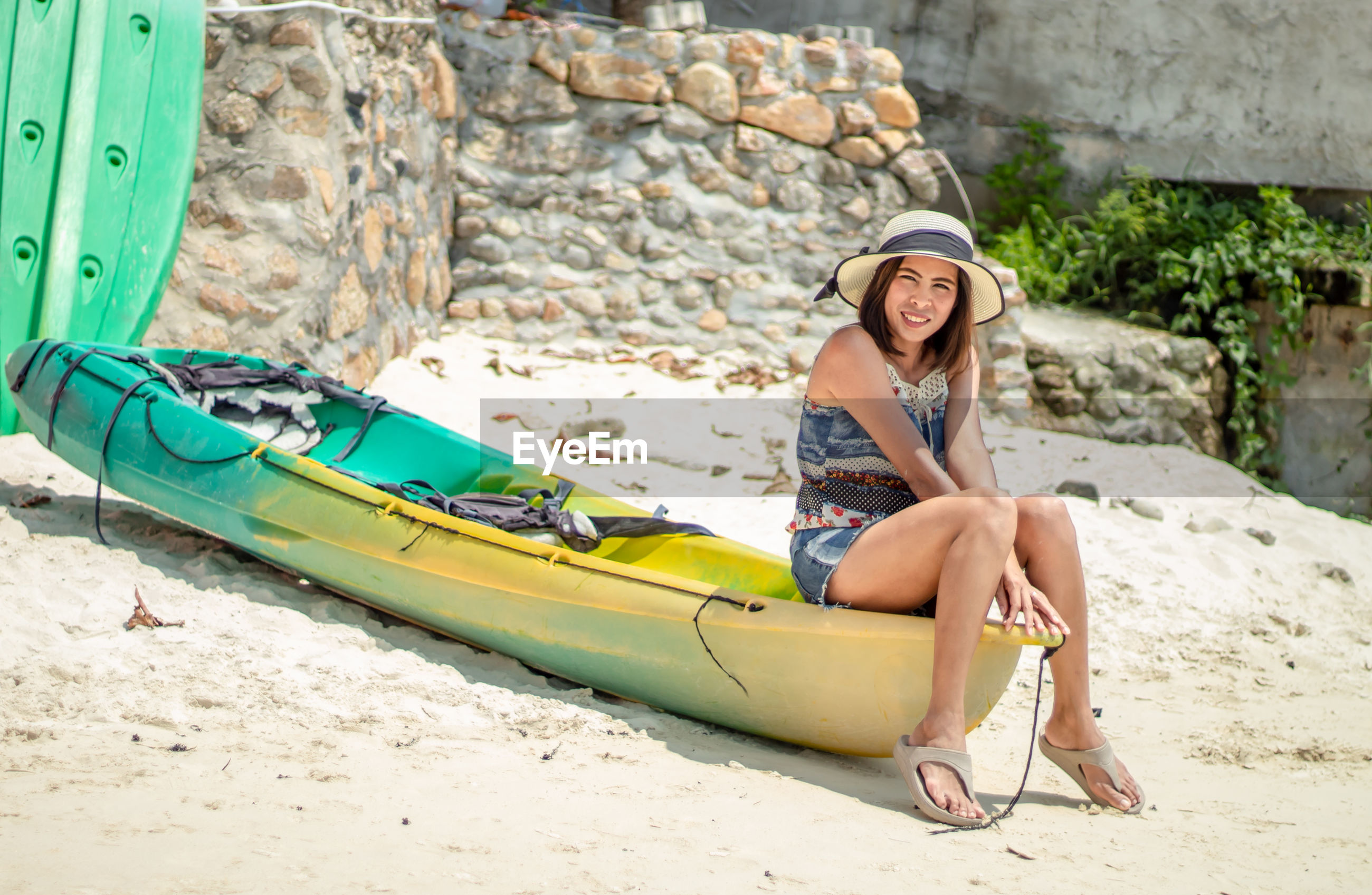 Full length of woman sitting on boat at beach