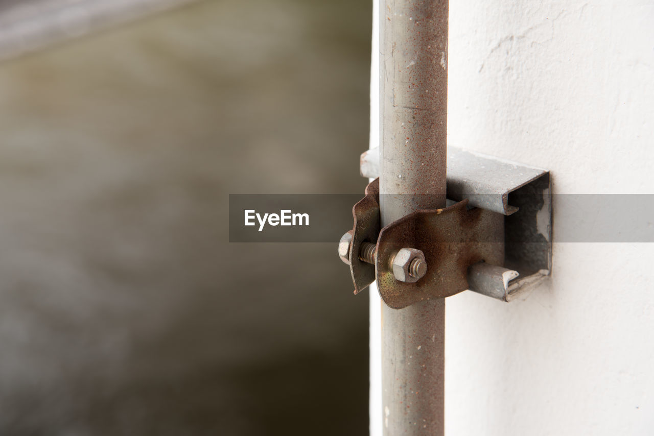 metal, close-up, no people, safety, protection, focus on foreground, day, security, outdoors, white color, connection, door, lock, wall - building feature, entrance, architecture, built structure, selective focus, rusty, pipe - tube, latch