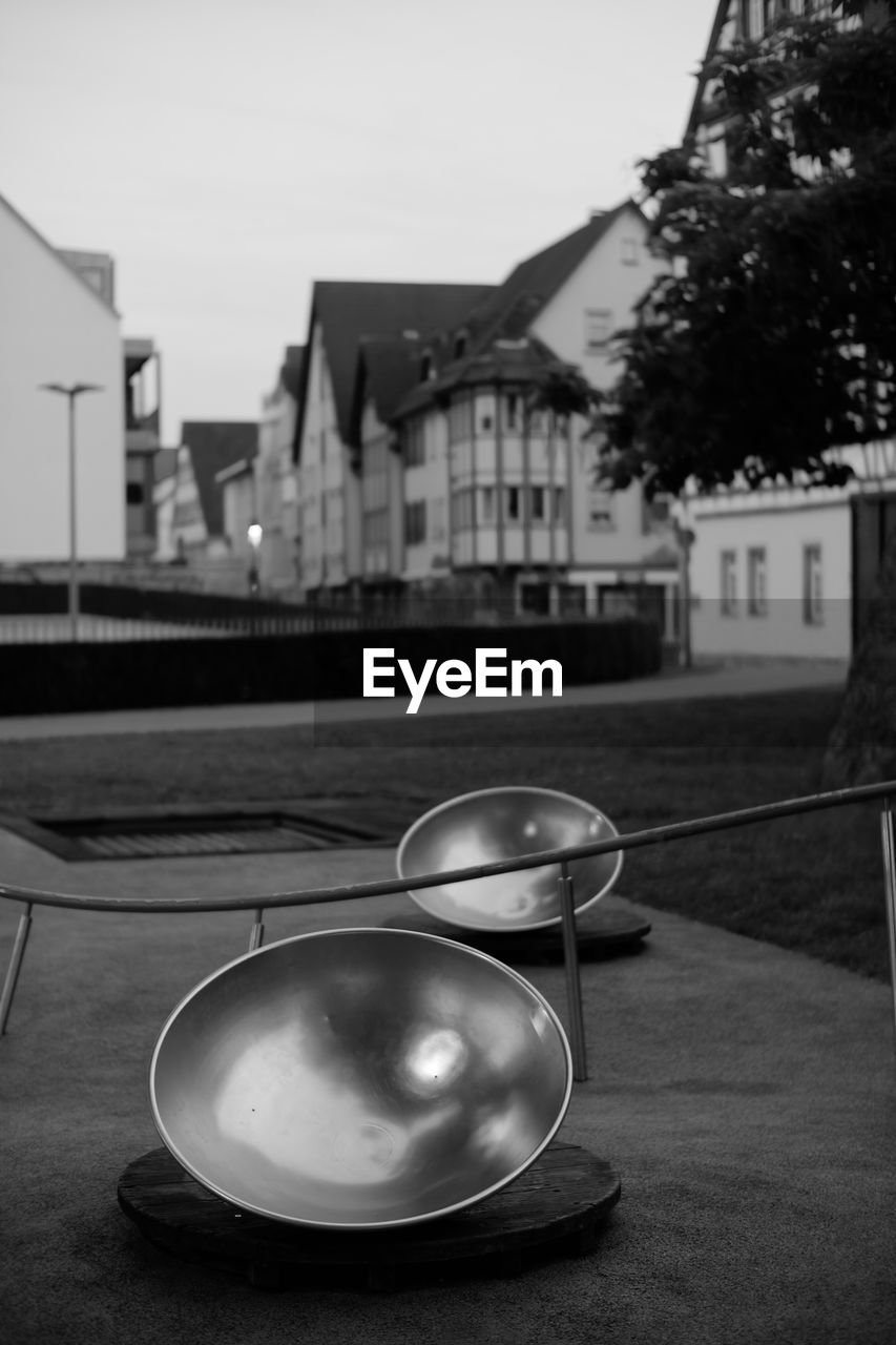 focus on foreground, architecture, built structure, building exterior, no people, table, close-up, kitchen utensil, sky, building, outdoors, day, nature, still life, city, railing, glasses, spoon, eating utensil, bowl, personal accessory