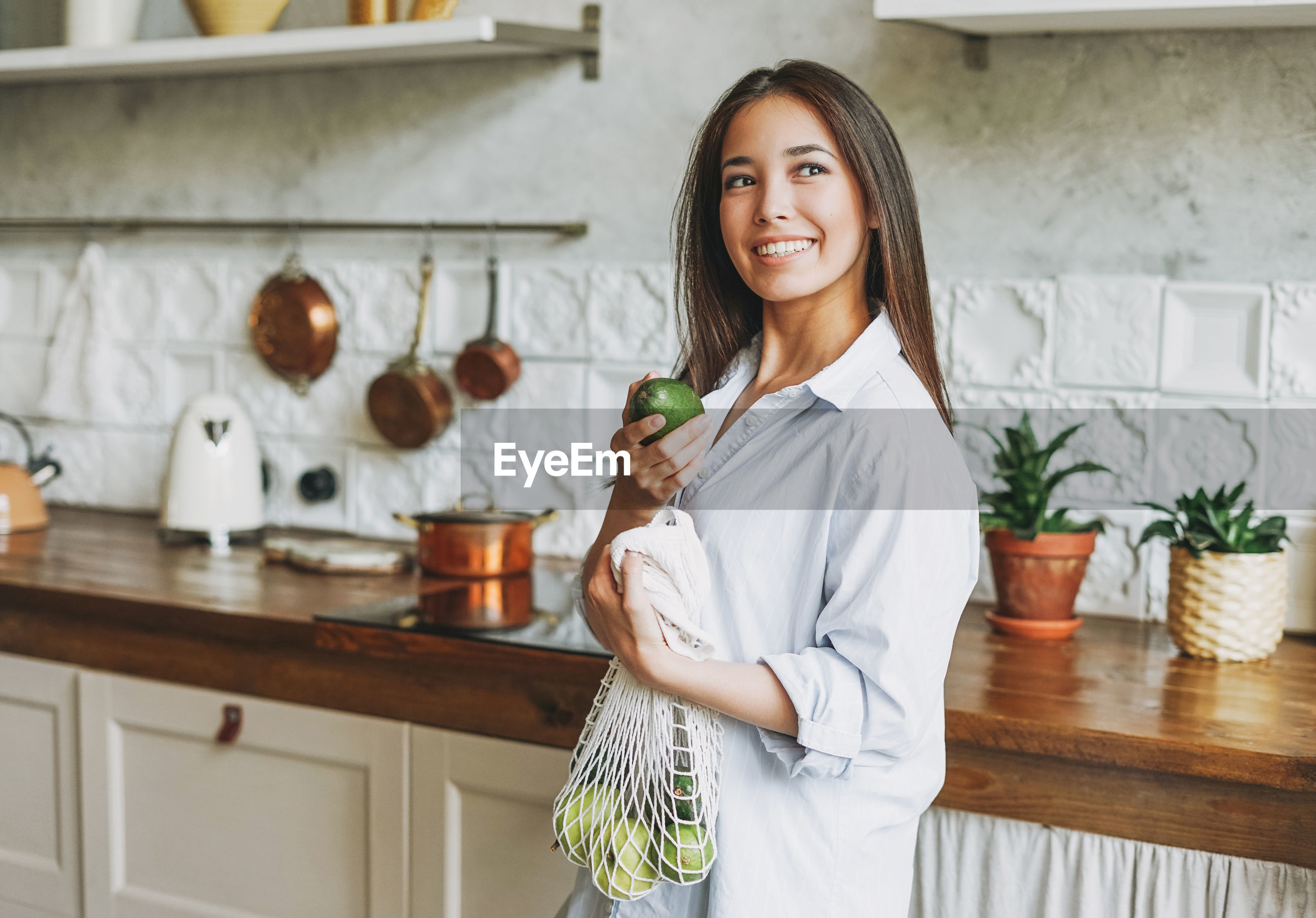 View of smiling woman holding fruit at home