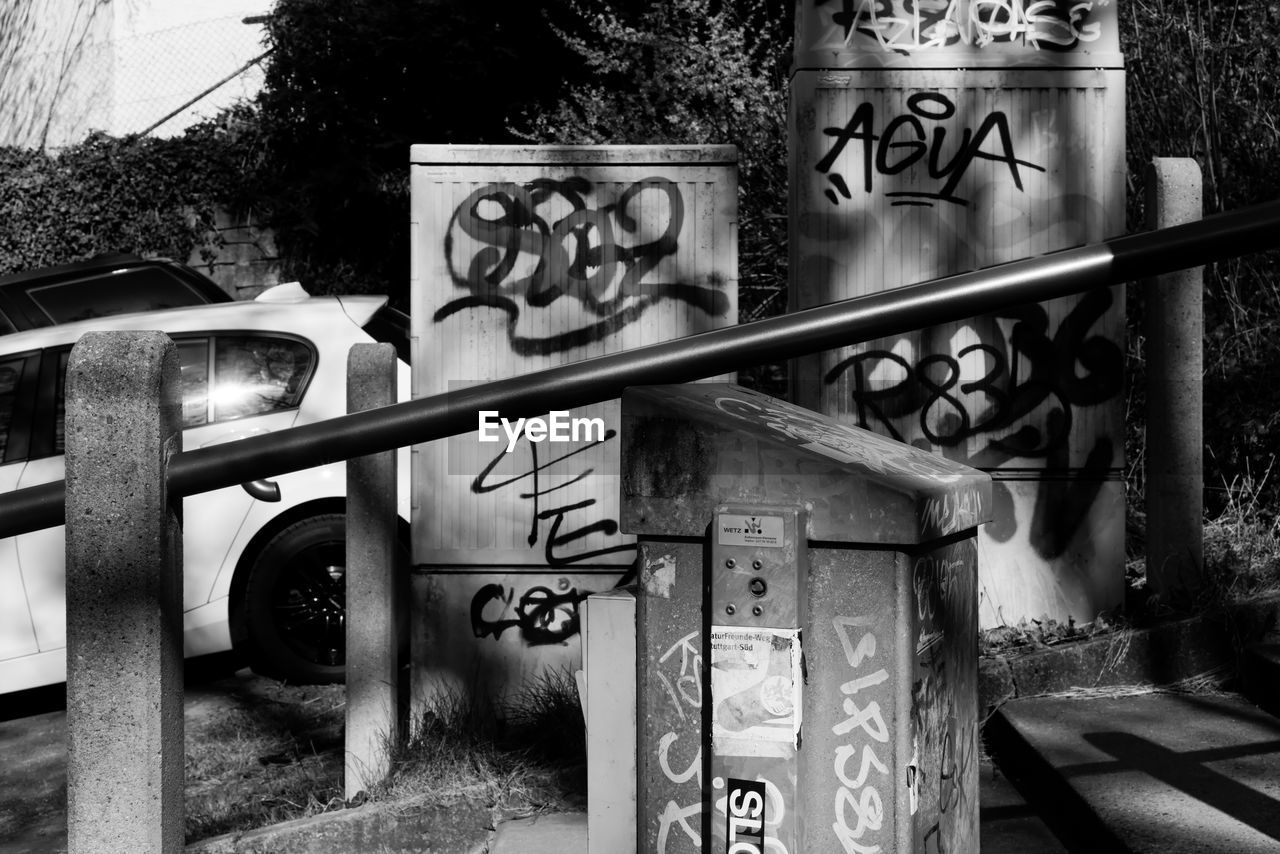 text, graffiti, western script, communication, day, no people, railing, outdoors, sign, nature, architecture, art and craft, creativity, representation, tree, built structure, gate, street art, plant