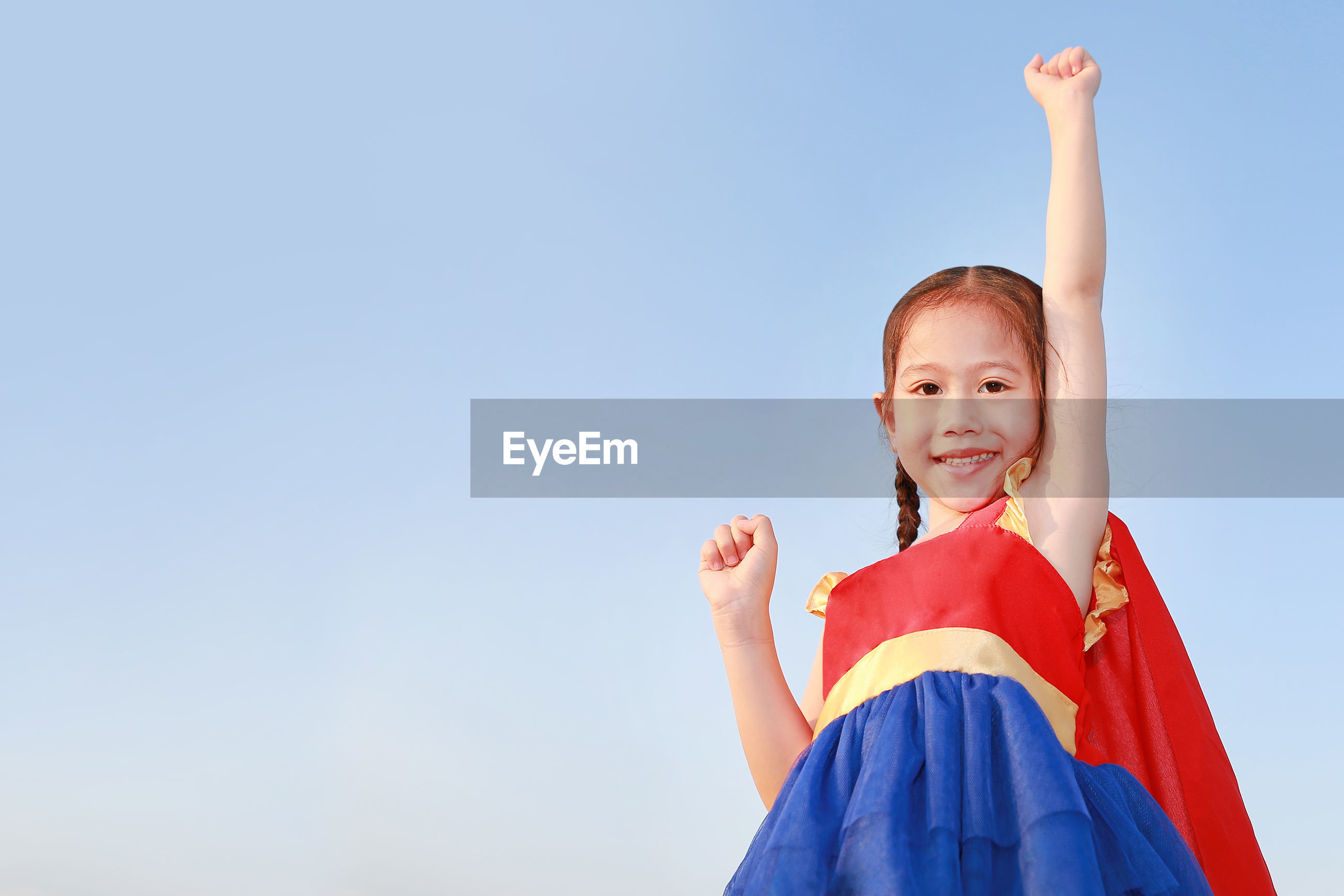 Low angle portrait of smiling girl with hand raised standing against clear blue sky