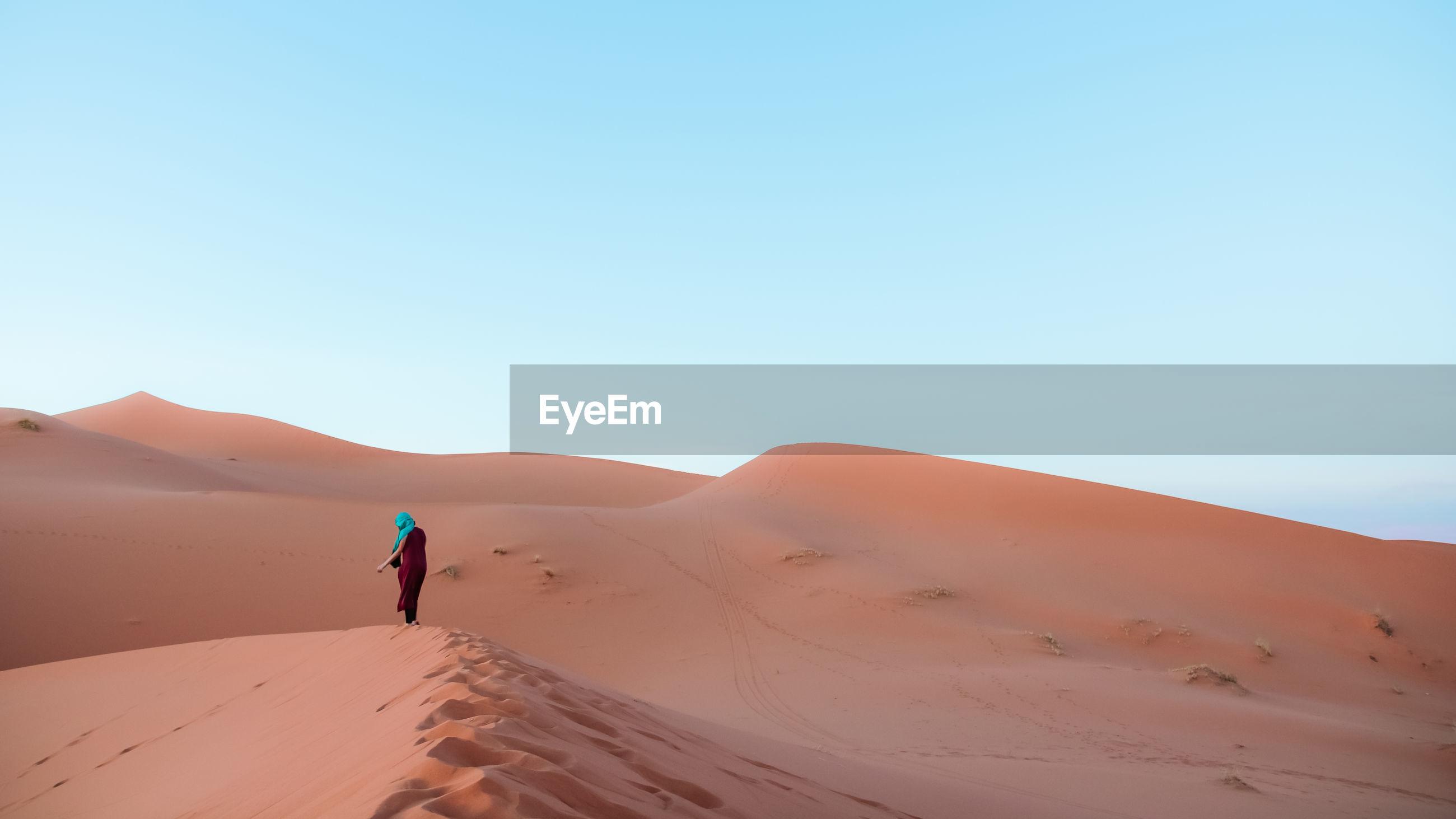 Full length of man walking on sand dune