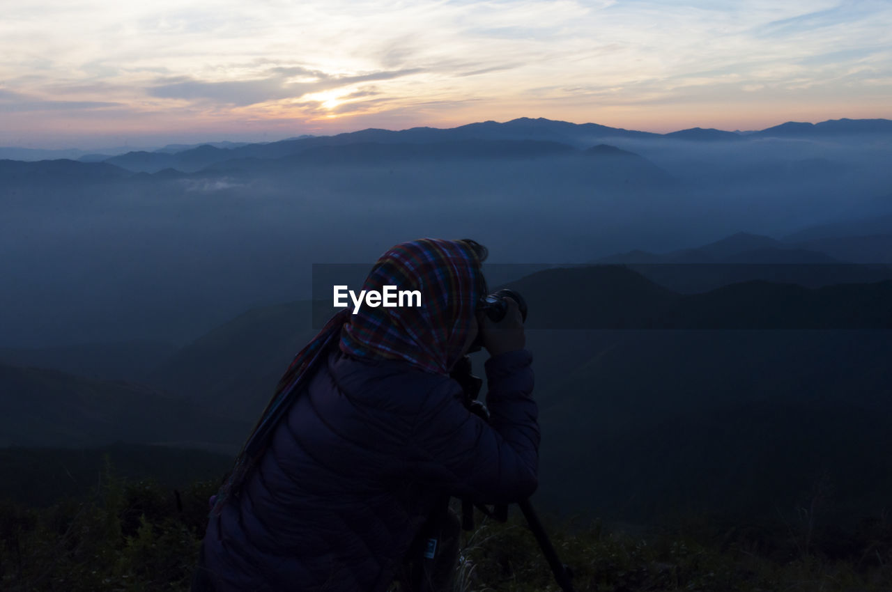 Rear View Of Woman Photographing Mountains Against Sky During Sunset