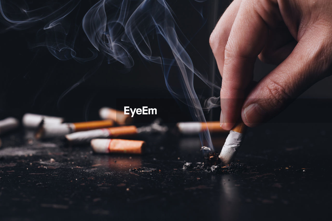 Cropped hand of person putting out cigarette against black background