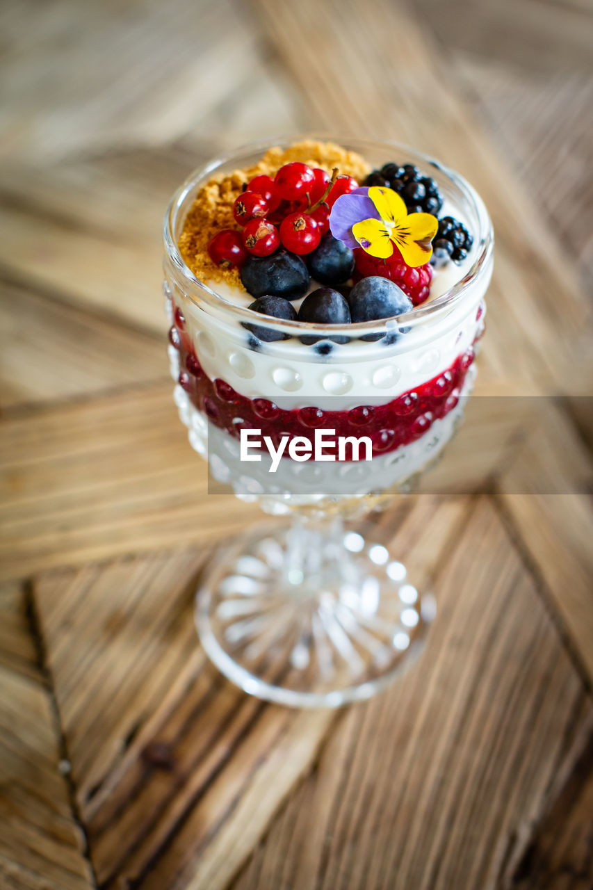 food, food and drink, fruit, table, healthy eating, wood - material, freshness, still life, berry fruit, high angle view, close-up, indoors, no people, sweet food, wellbeing, indulgence, temptation, focus on foreground, ready-to-eat, blueberry, glass, red currant