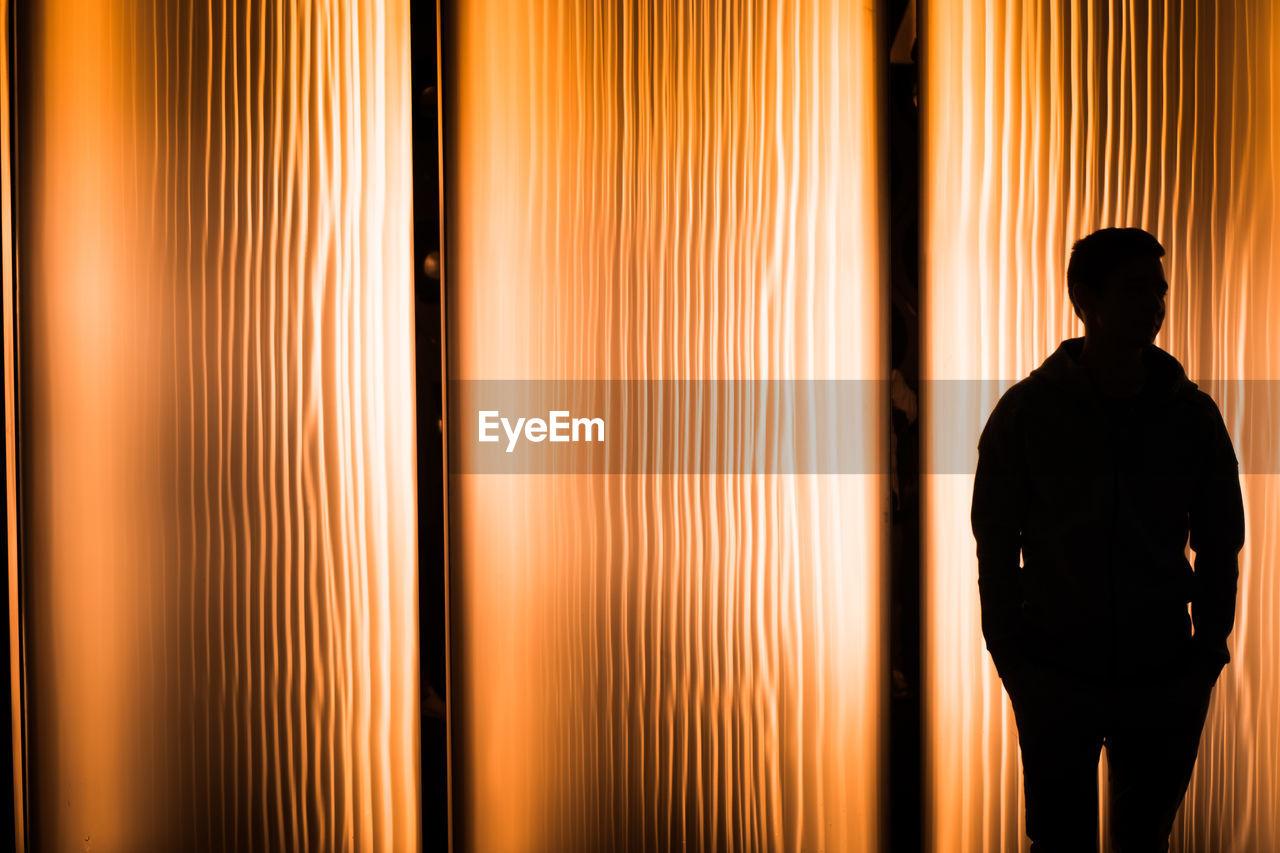 Silhouette man standing against illuminated curtain