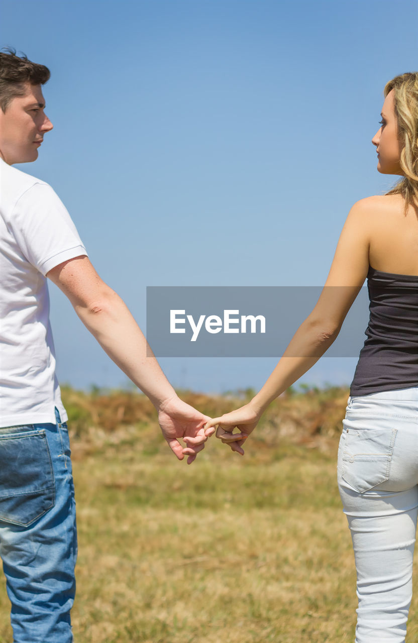 MIDSECTION OF COUPLE STANDING ON LAND