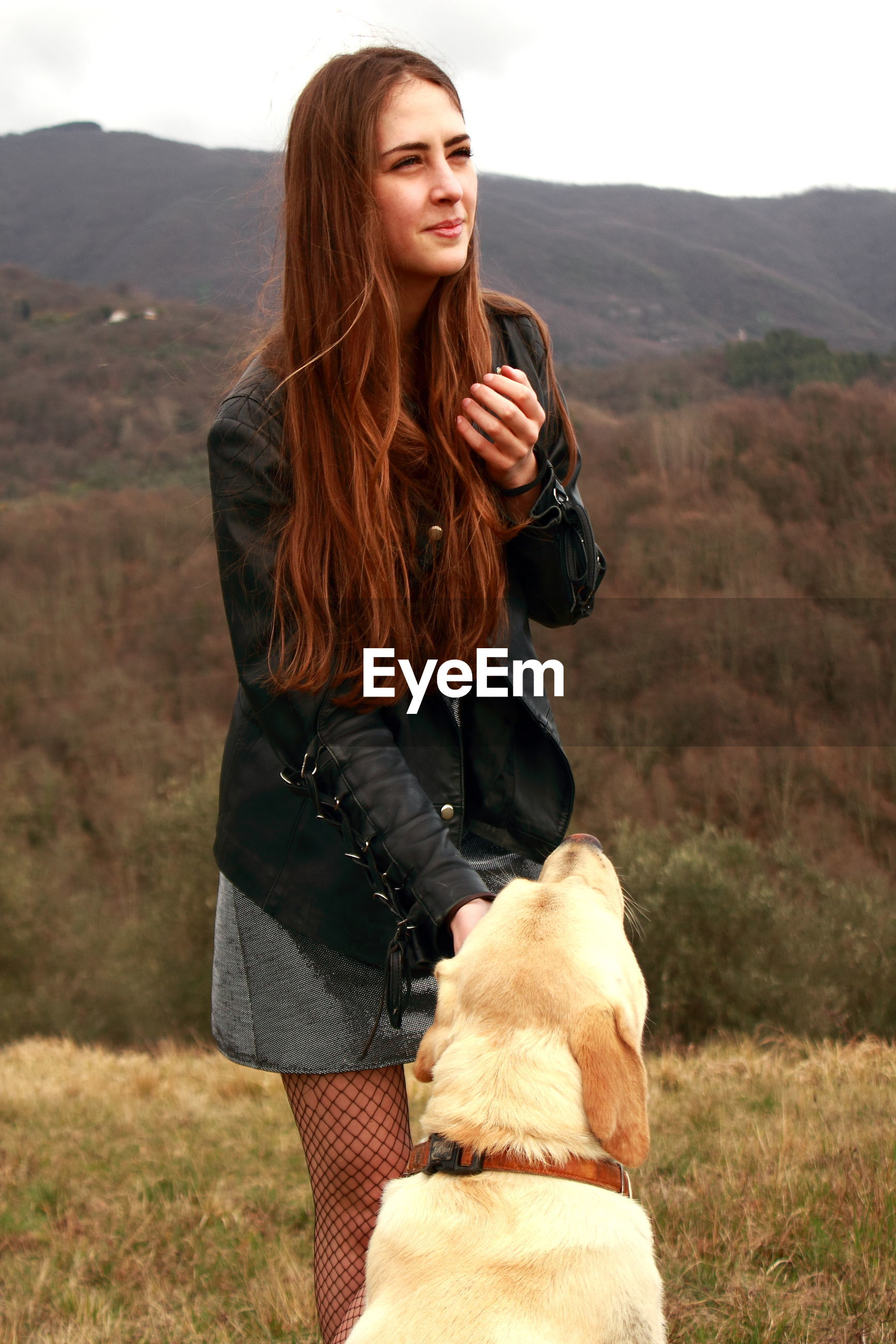 Young woman with dog standing on mountain