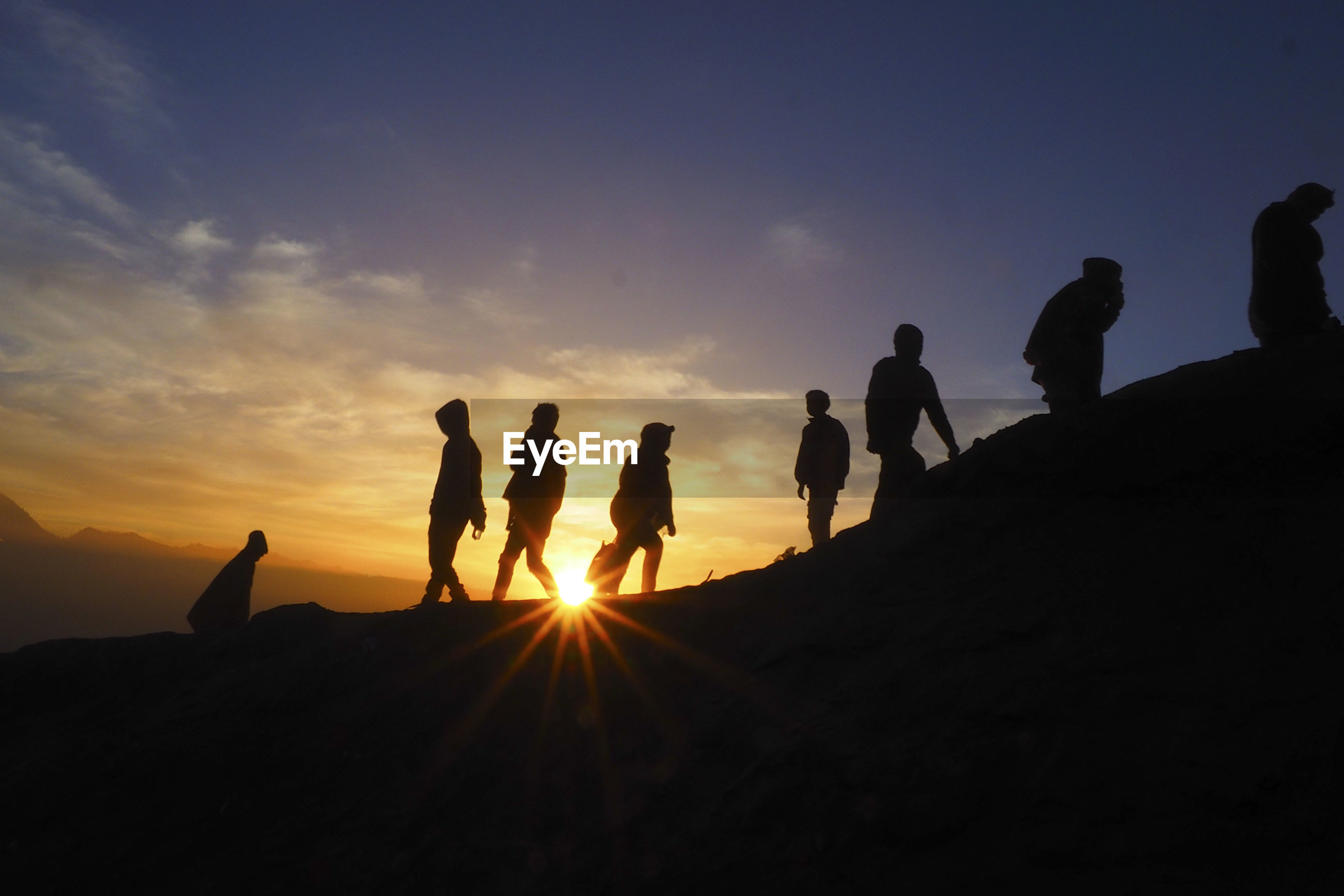 Silhouette people hiking on mountain against sky during sunset