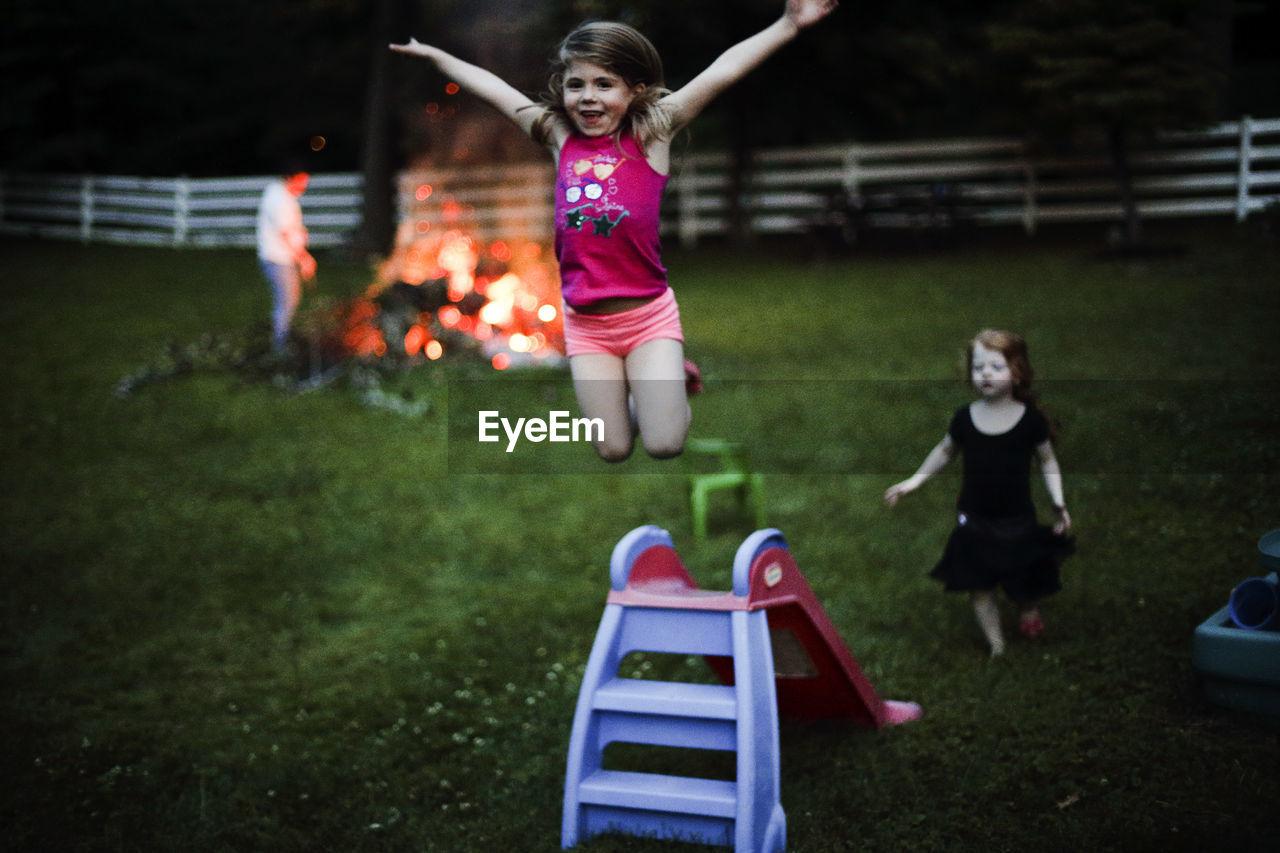 Girl Jumping From Slide In Backyard