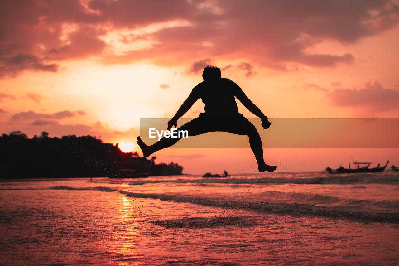 SILHOUETTE MAN JUMPING IN SEA AGAINST ORANGE SKY
