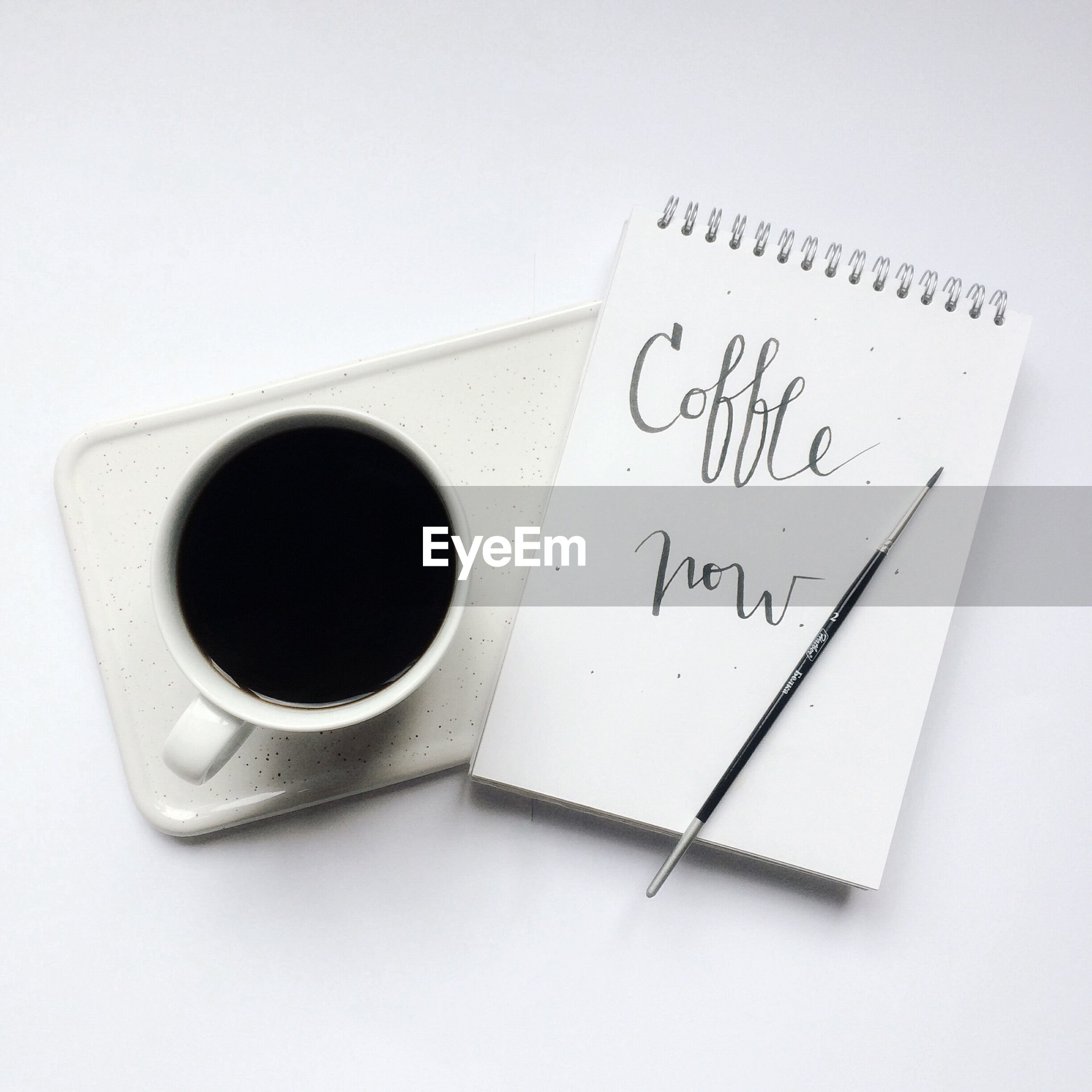 Directly above shot of coffee cup and note pad over white background