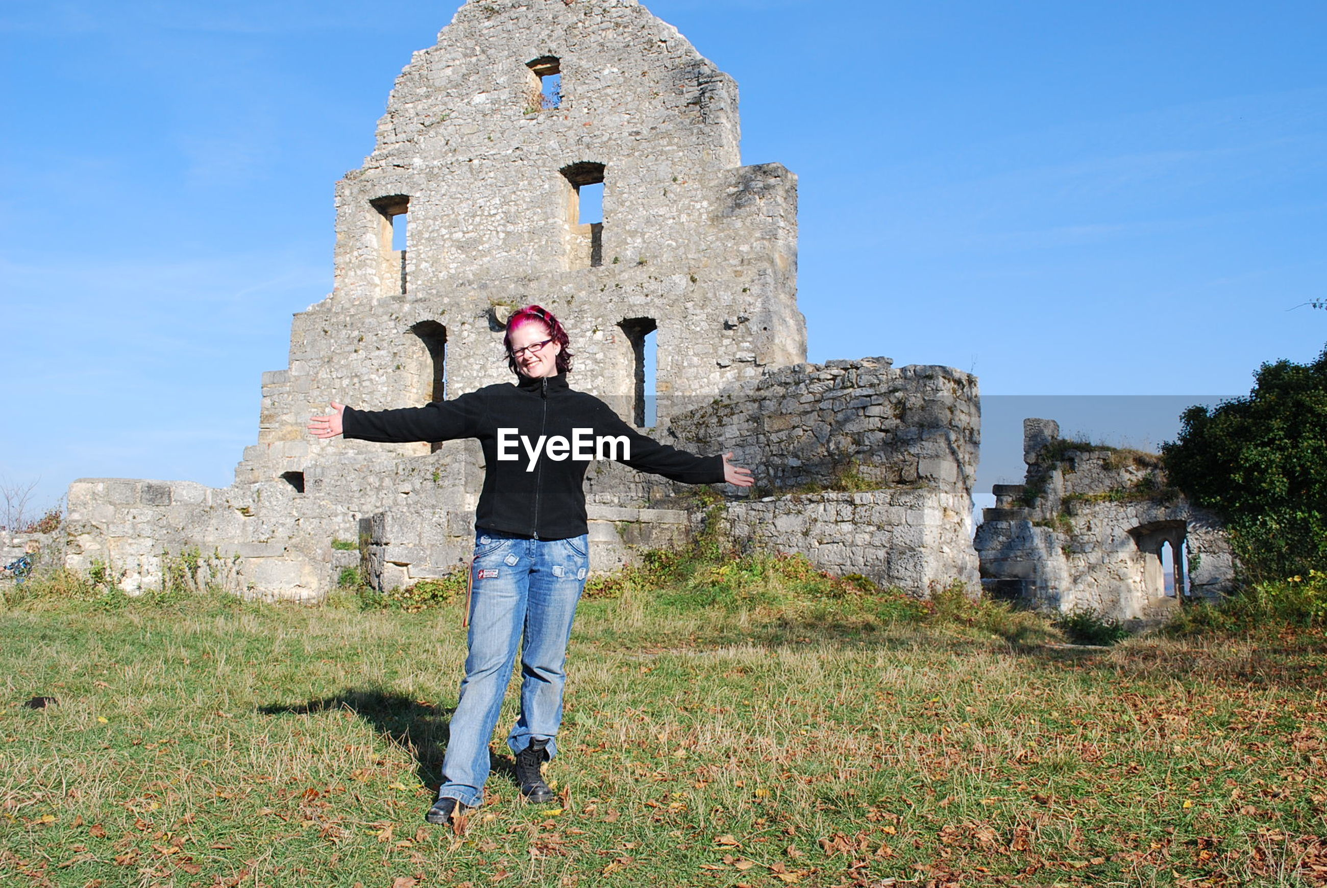 Woman standing against old ruin