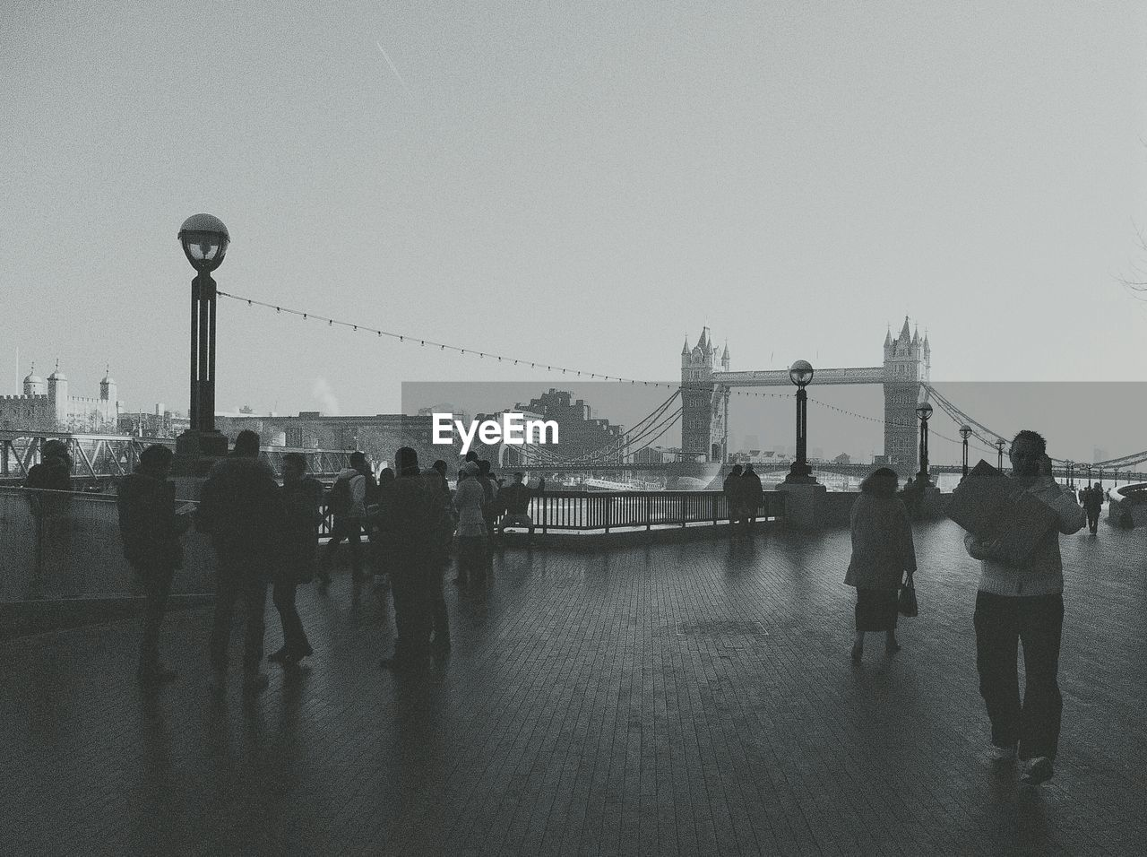 People at promenade with tower bridge against sky
