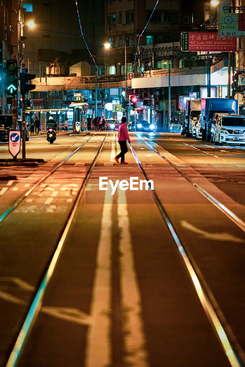 illuminated, night, transportation, city, architecture, one person, mode of transportation, street, road, built structure, real people, car, building exterior, city life, motor vehicle, lifestyles, full length, land vehicle, direction, the way forward, outdoors