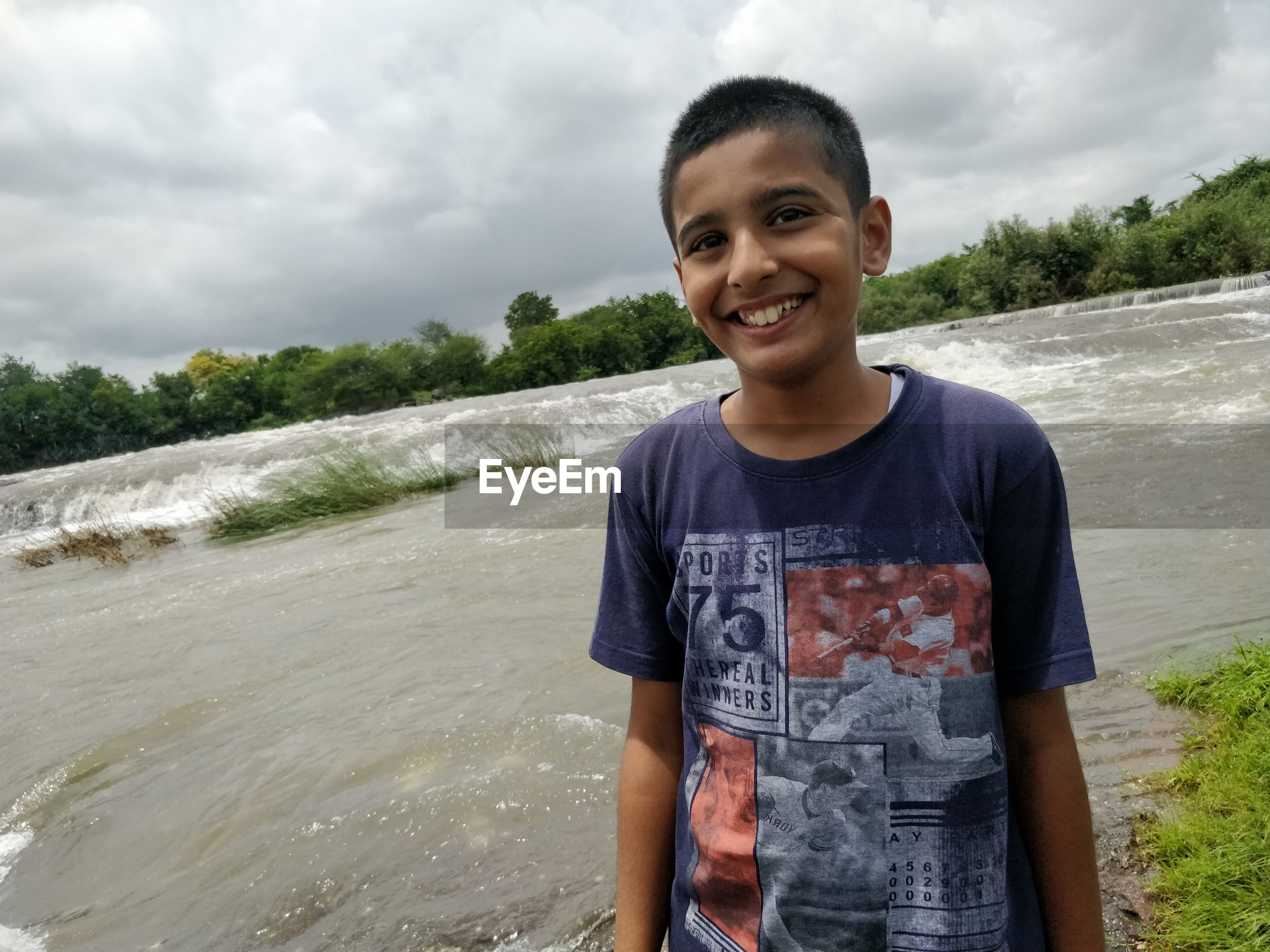 Portrait of smiling boy standing against waterfall