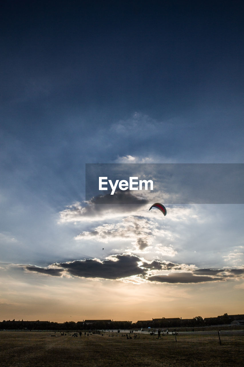 sky, parachute, sunset, adventure, real people, one person, nature, paragliding, cloud - sky, mid-air, flying, scenics, outdoors, beauty in nature, landscape, extreme sports, lifestyles, day, people